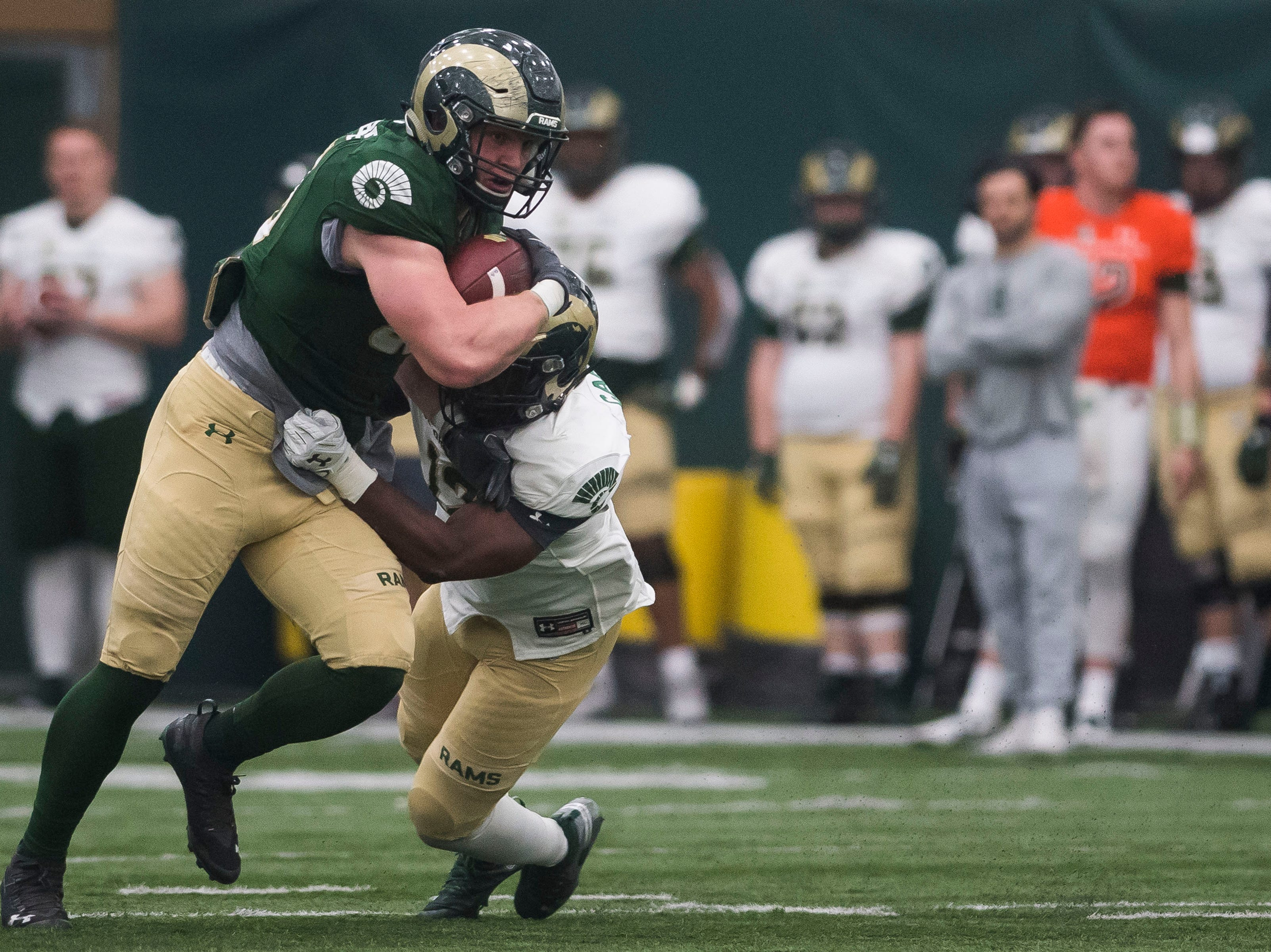 CSU sophomore tight end Trey McBride (85) is tackled by sophomore linebacker Cam'ron Carter (12) during CSU's Spring game on Thursday, March 14, 2019, at their indoor practice facility in Fort Collins, Colo.