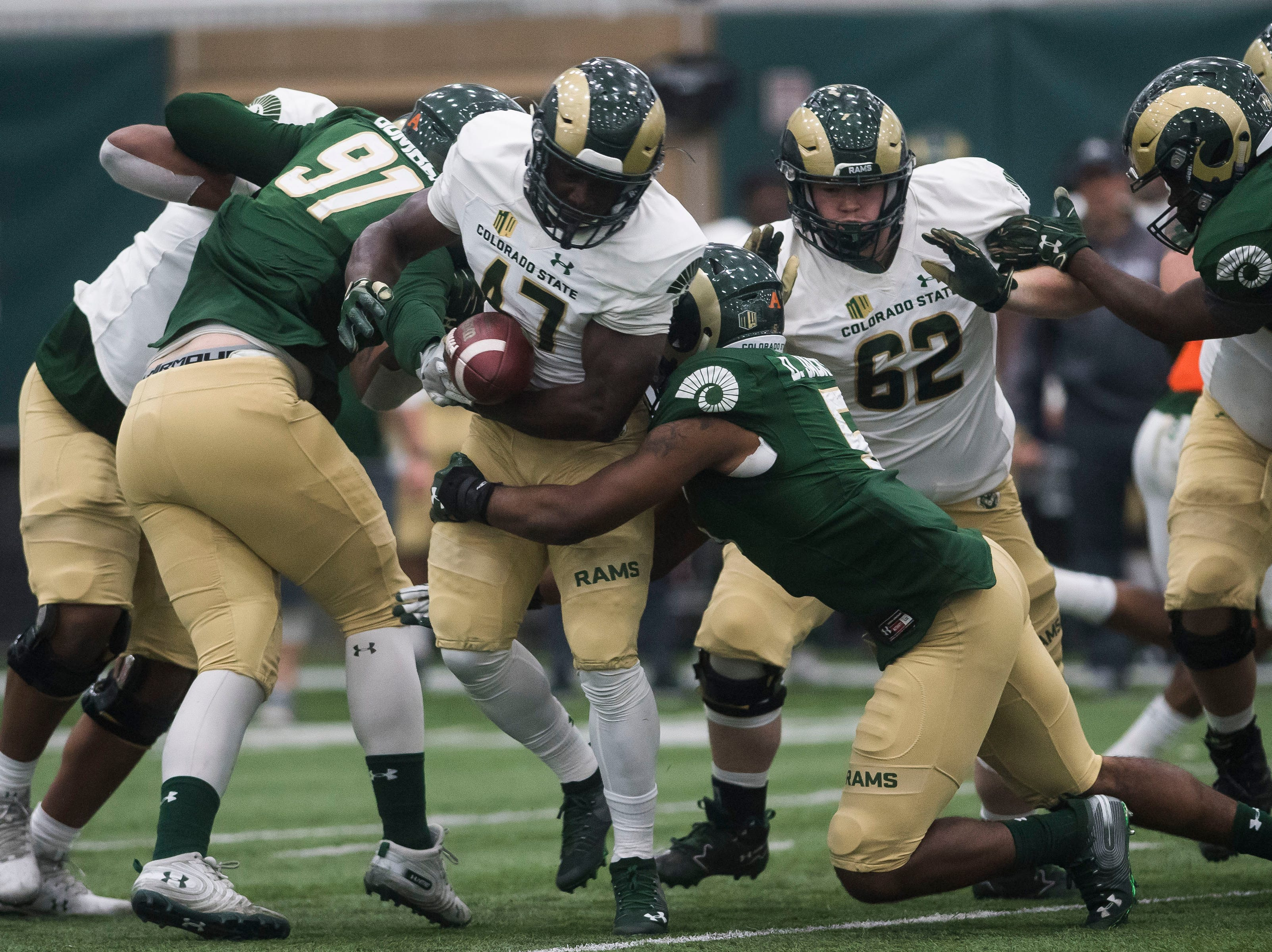 CSU freshman running back David Aggrey (47) nearly loses the ball while being tackled by sophomore linebacker Dequan Jackson (5) during CSU's Spring game on Thursday, March 14, 2019, at their indoor practice facility in Fort Collins, Colo.
