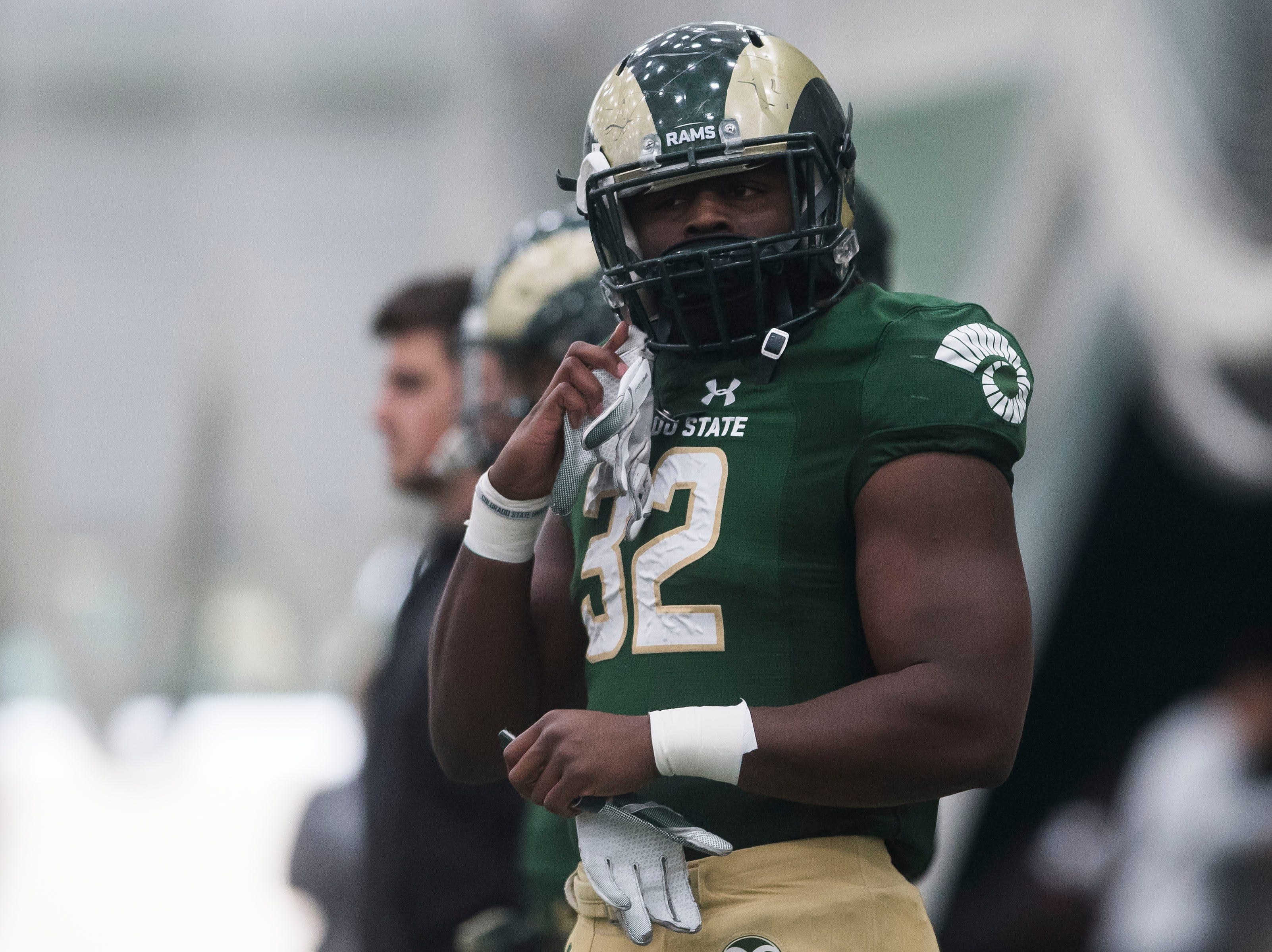 CSU junior running back Marcus McElrow (32) pulls his gloves off his helmet during drills preceding CSU's Spring game on Thursday, March 14, 2019, at their indoor practice facility in Fort Collins, Colo.