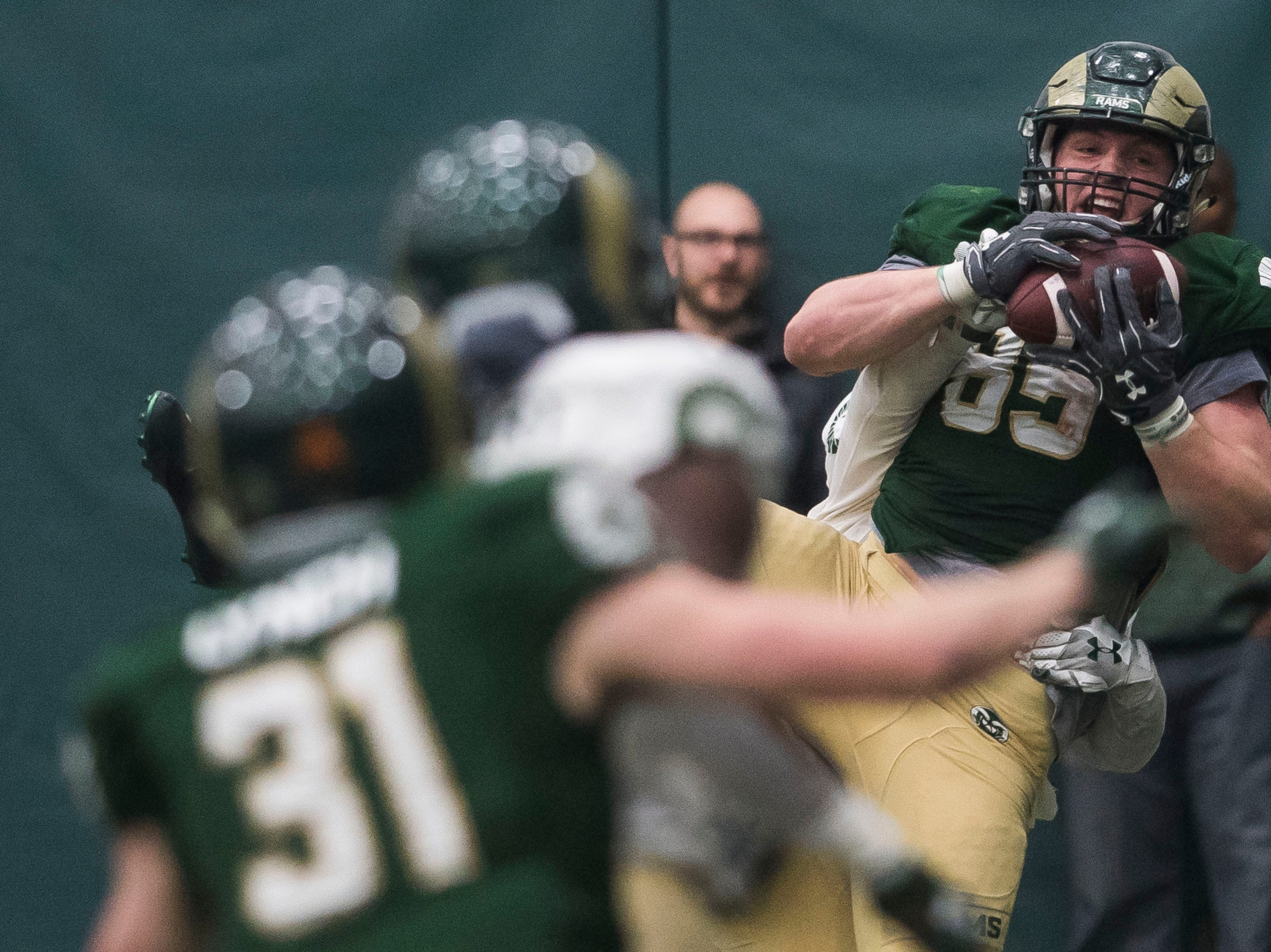 CSU sophomore tight end Trey McBride (85) pulls in a touchdown reception while sophomore cornerback Adonis Rufran (38) tackles him during CSU's Spring game on Thursday, March 14, 2019, at their indoor practice facility in Fort Collins, Colo.