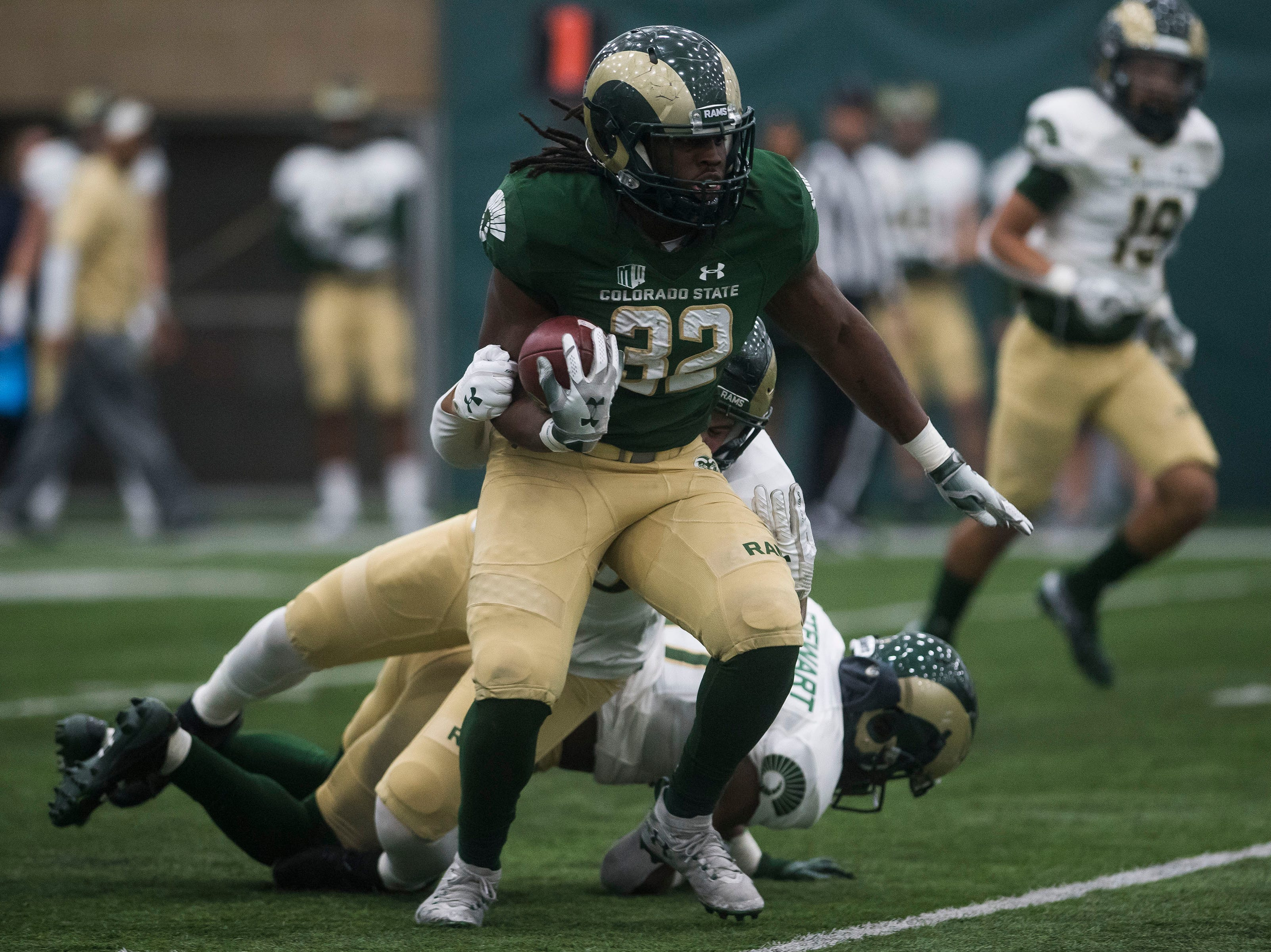 CSU junior running back Marcus McElroy (32) steps out of a tackle by sophomore linebacker Corte Tapia (50) during CSU's Spring game on Thursday, March 14, 2019, at their indoor practice facility in Fort Collins, Colo.