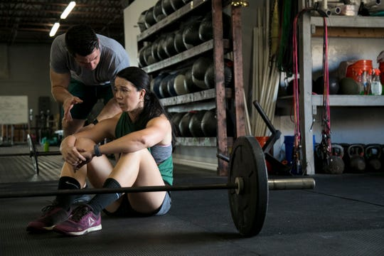 Eric Fay instructs Annabelle Tometich on muscle ups as she recovers from the first half of the CrossFit Open 19.4 workout on Friday, March 15, 2019, at CrossFit 239 in Fort Myers.