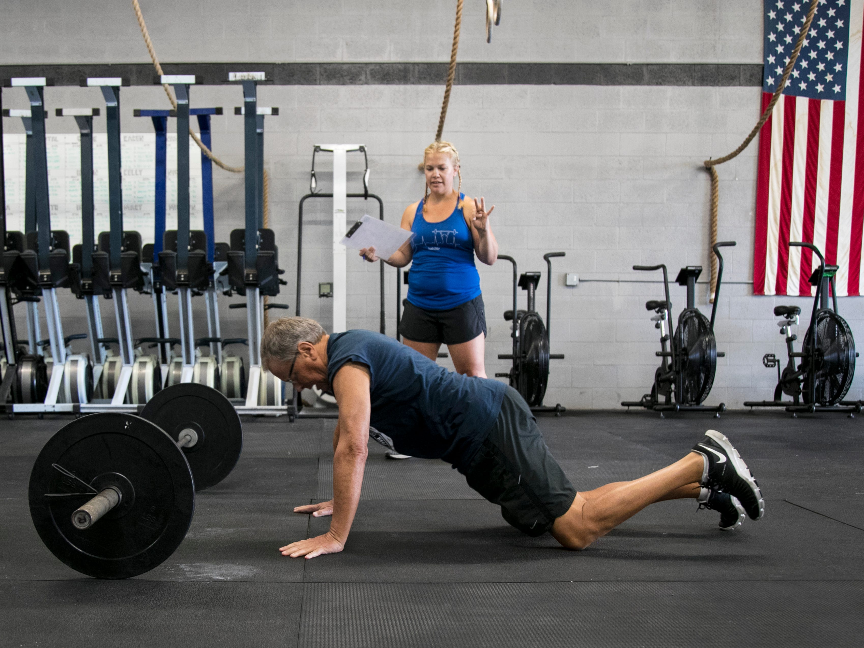 Bill Hanney, 62, does burpees as Lynn Schneider counts his reps during the CrossFit Open 19.4 workout on Friday, March 15, 2019, at CrossFit 239 in Fort Myers.