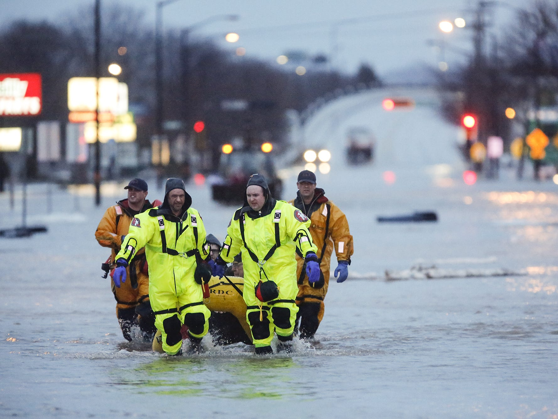 Firefighters rescue a group of people out of a flooded area Thursday, March 14, 2019 on Johnson Street in Fond du Lac Wis. Thursday, March 14, 2019. Ice jams on the east branch of the Fond du Lac River and heavy rain caused widespread flooding problems in the city. Doug Raflik/USA TODAY NETWORK-Wisconsin