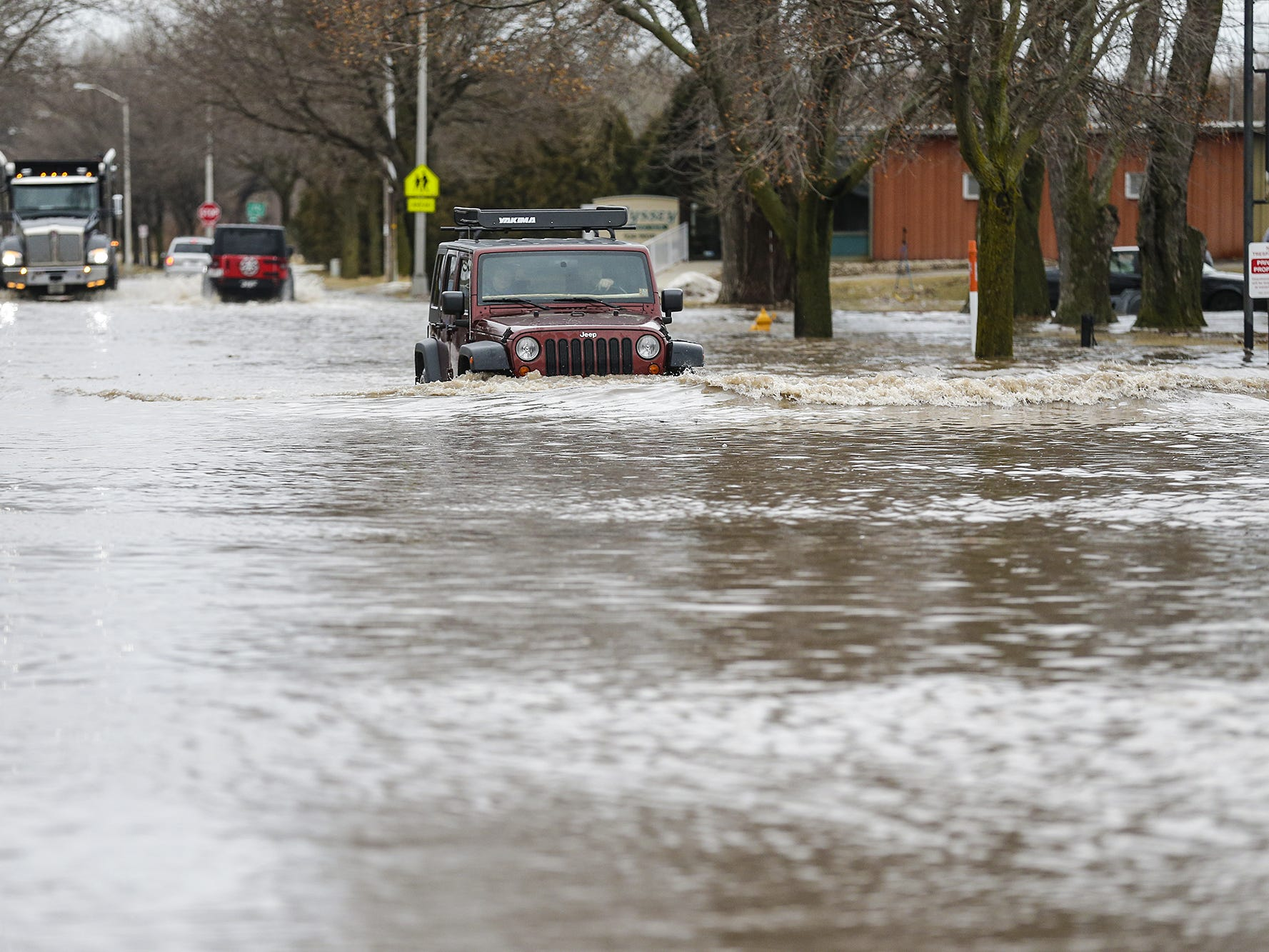 A jeep is driven down a flooded Hickory Street Thursday, March 14, 2019 in Fond du Lac, Wis. Ice jams on the east branch of the Fond du Lac River and heavy rain caused widespread flooding problems in the city. Doug Raflik/USA TODAY NETWORK-Wisconsin