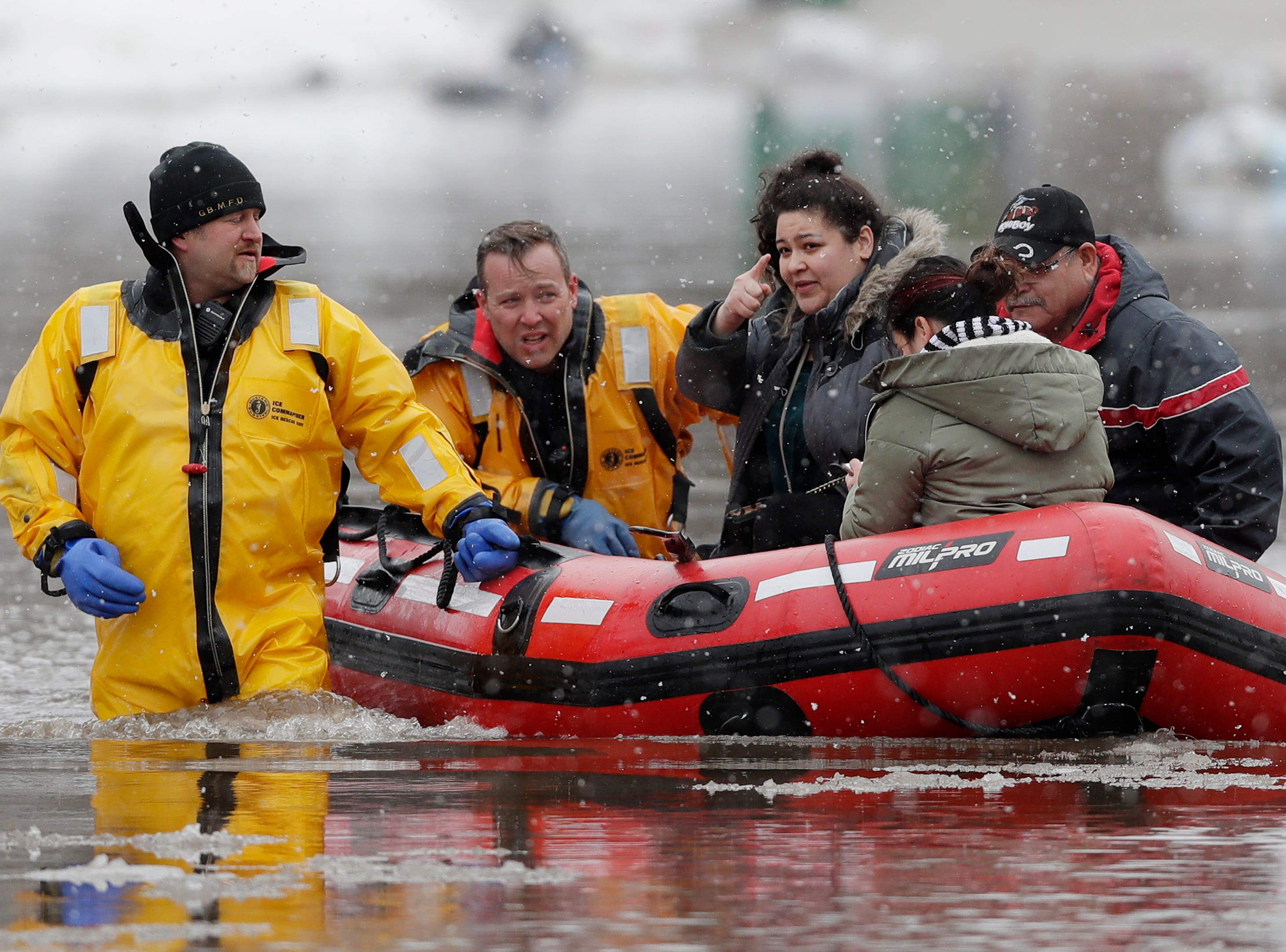 Green Bay firefighters assist residents in evacuating their homes due to East river floodwaters on Friday, March 15, 2019 in Green Bay, Wis.