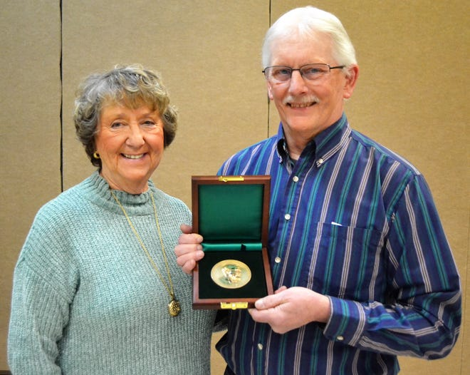 Eugene Stamsta of Oconto holds his medal from the Carnegie Hero Fund Commission, awarded at the Oconto City Council meeting on March 12, for his rescue of Anne Nerenhausen, left, from the Oconto River in July 2017.