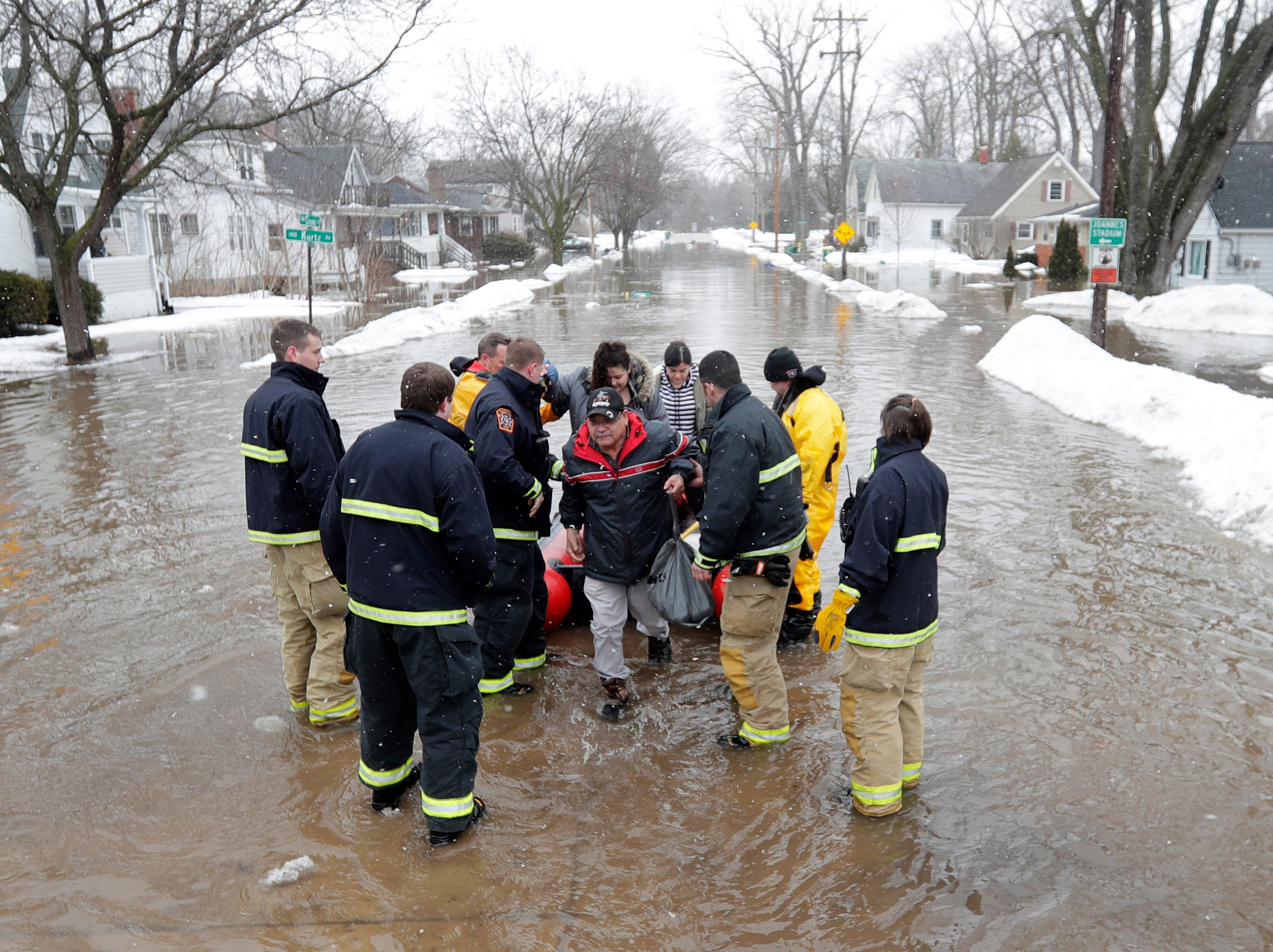 Firefighters assist residents on Crooks Street with evacuations due to the East river flooding on Friday, March 15, 2019 in Green Bay, Wis.