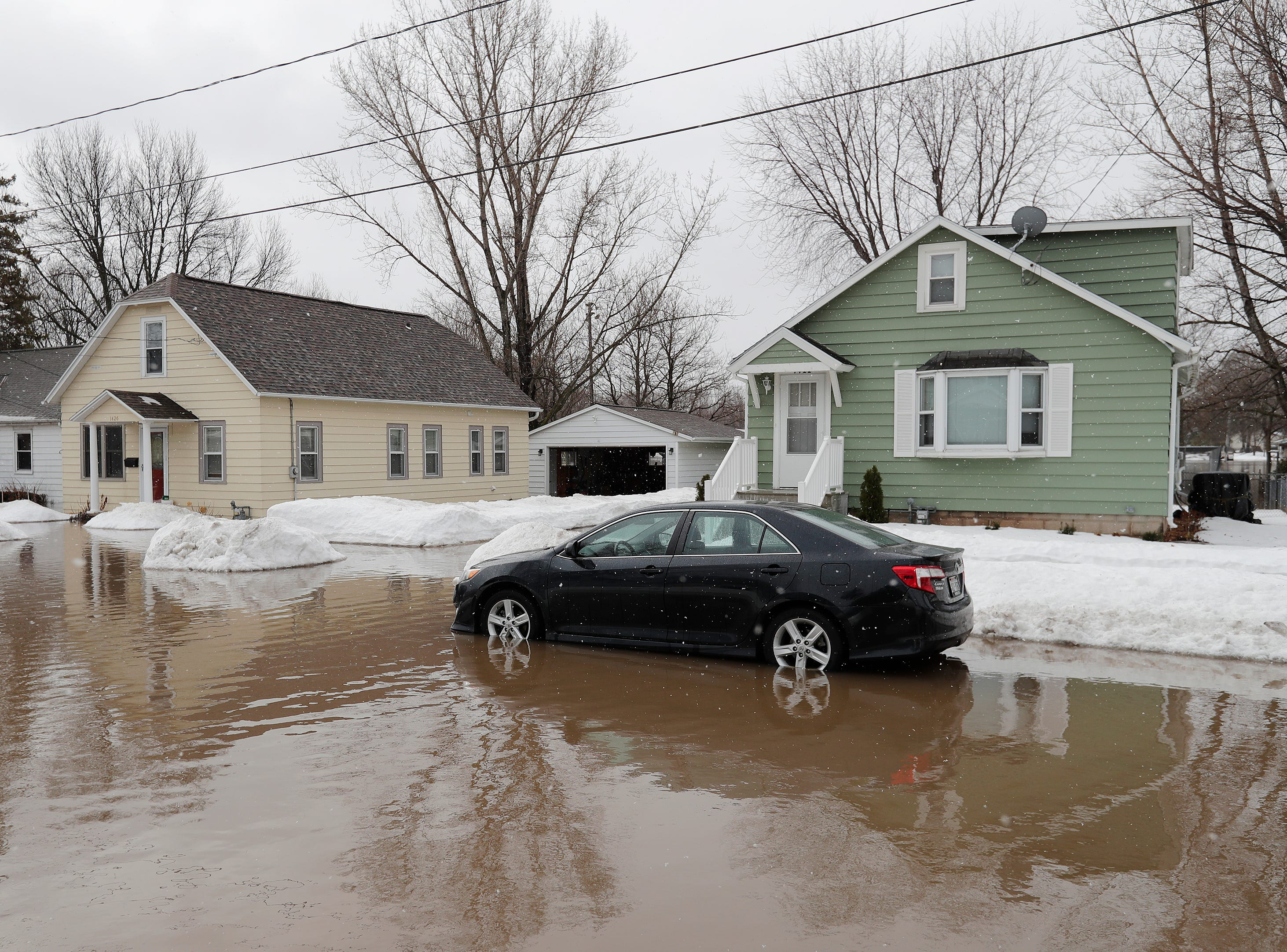 A car sits in standing floodwaters from the East river on Friday, March 15, 2019 in Green Bay, Wis.