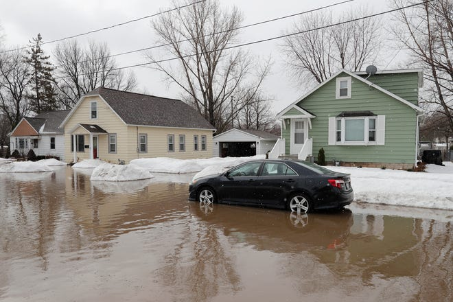A car sits in standing floodwaters from the East river on Friday, March 15, 2019, in Green Bay, Wis.