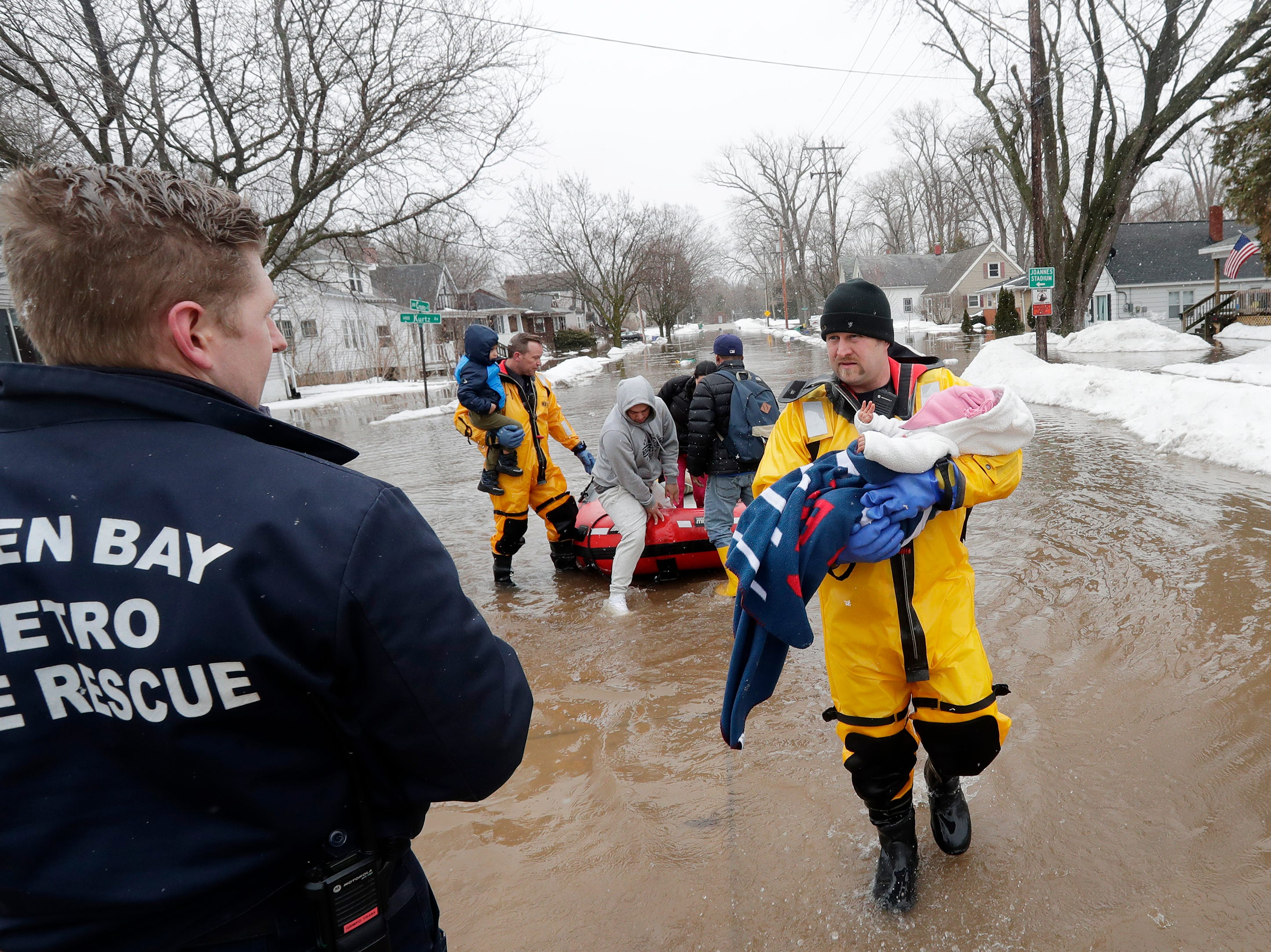 Firefighter Brian Farr carries a baby from the boat as the GBFD assisted residents with home evacuations on Crooks Street due to the East river flooding on Friday, March 15, 2019 in Green Bay, Wis.