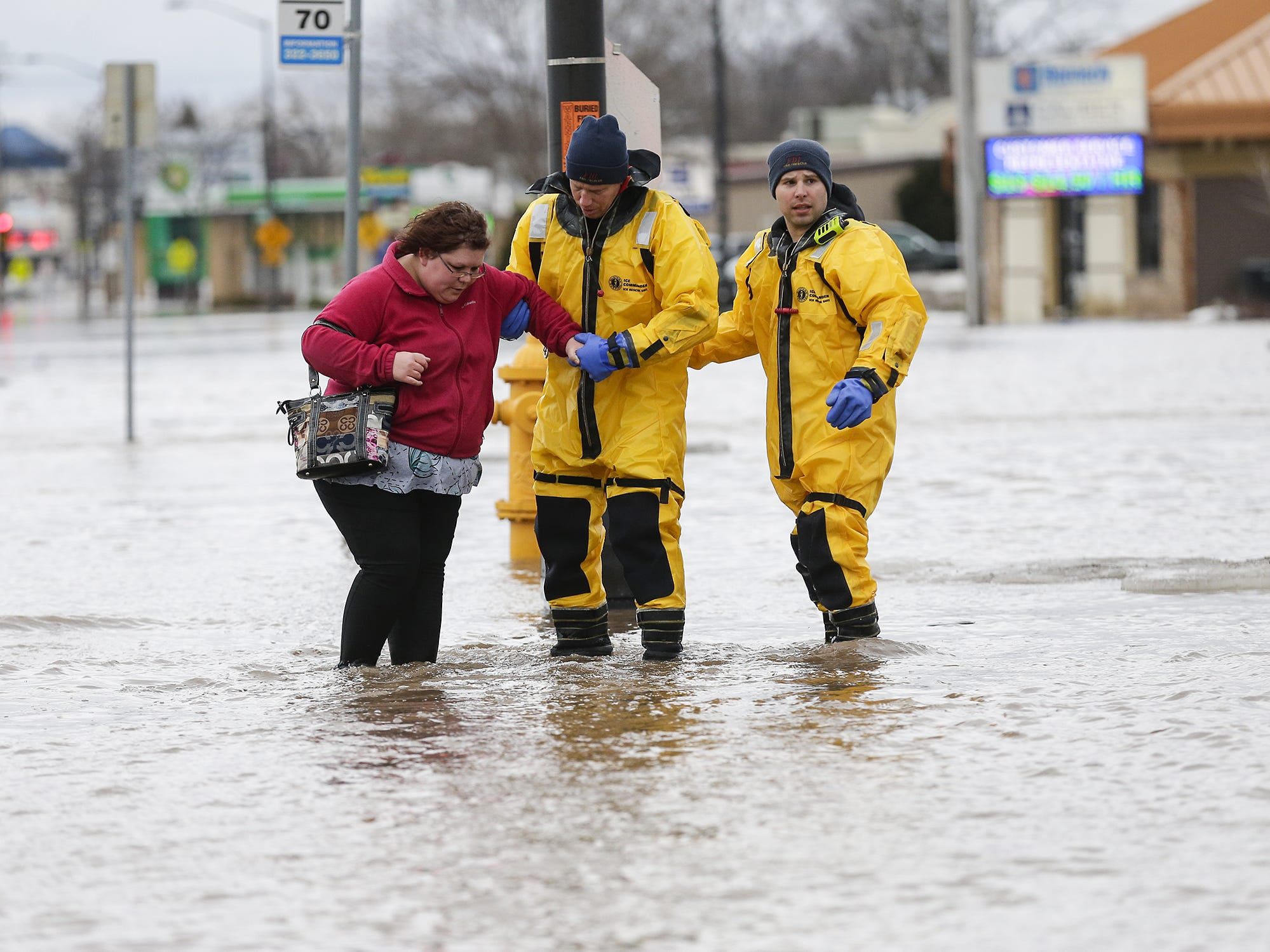 Mandi Mathews of Fond du Lac is helped out of a flooded area Thursday, March 14, 2019 on Johnson Street in Fond du Lac, Wis. Ice jams on the east branch of the Fond du Lac River and heavy rain caused widespread flooding problems in the city. Doug Raflik/USA TODAY NETWORK-Wisconsin