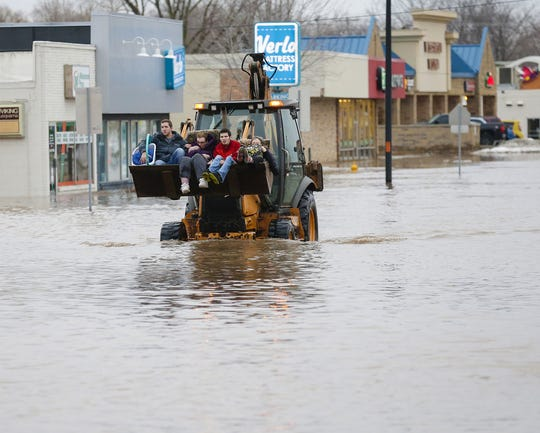 Linda Patt, second from left, is driven to safety in the bucket of a front end loader Thursday as she was rescued from flooded Georgetown Cleaners at 441 W. Johnson Street.