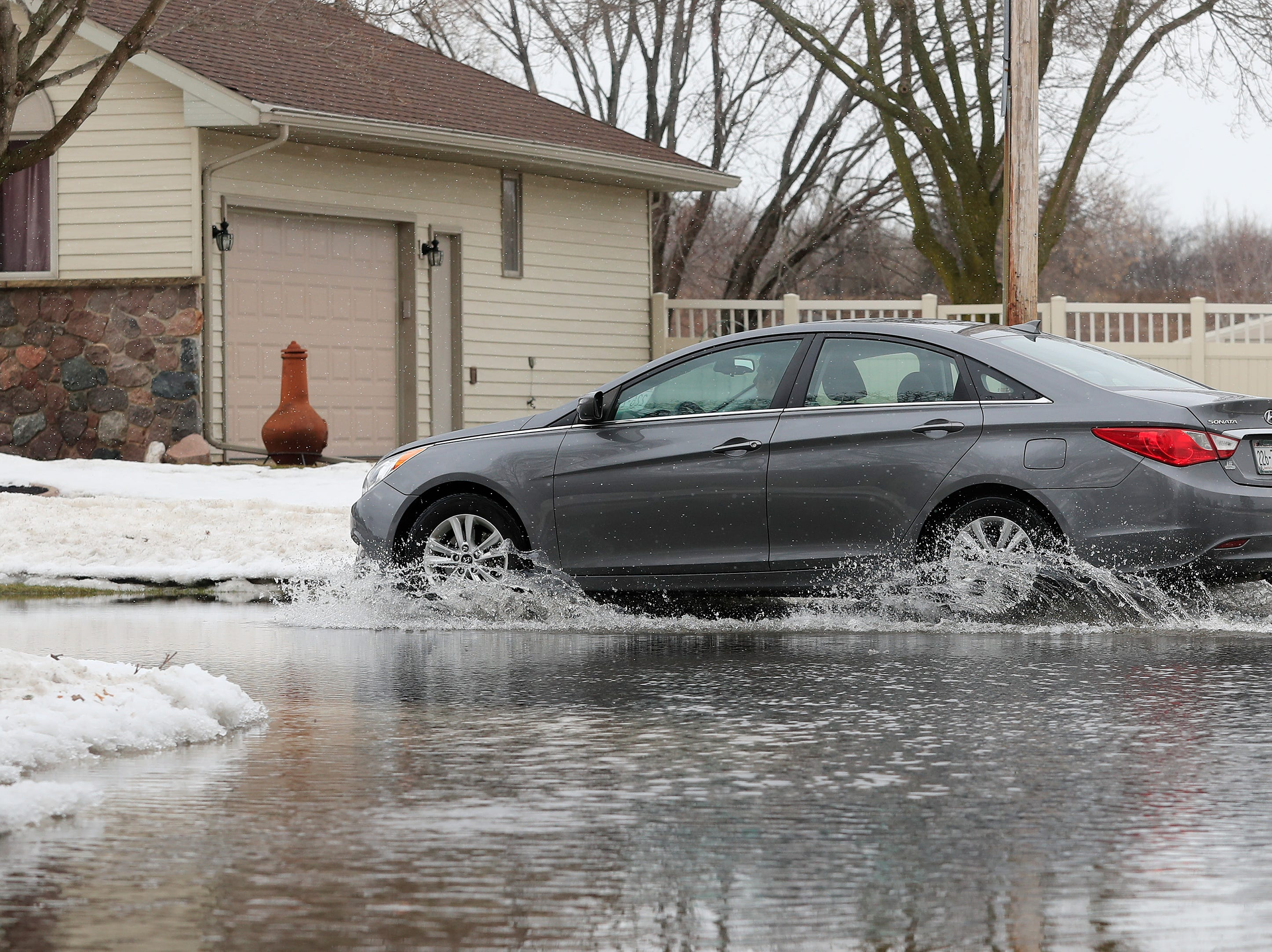 A motorist drives through a partially flooded intersection on Friday, March 15, 2019 in Allouez, Wis.