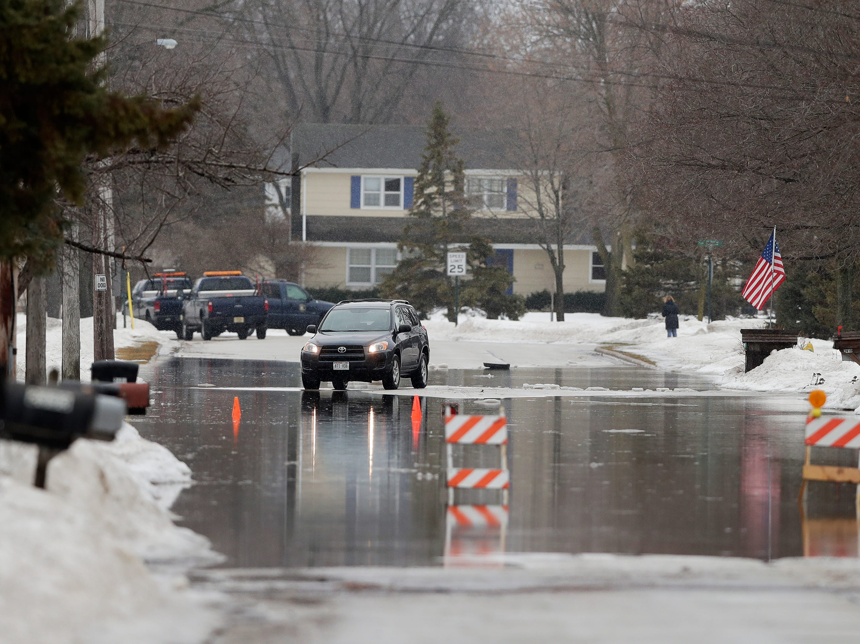 A flooded residential street is shown on Friday, March 15, 2019 in Allouez, Wis.