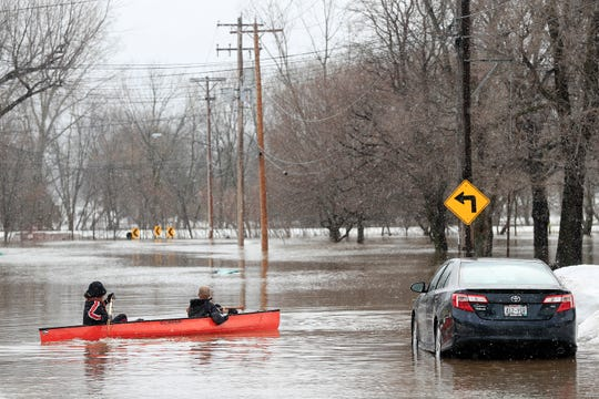 Residents launch a canoe from their driveway on Friday, March 15, 2019 in Green Bay, Wis.