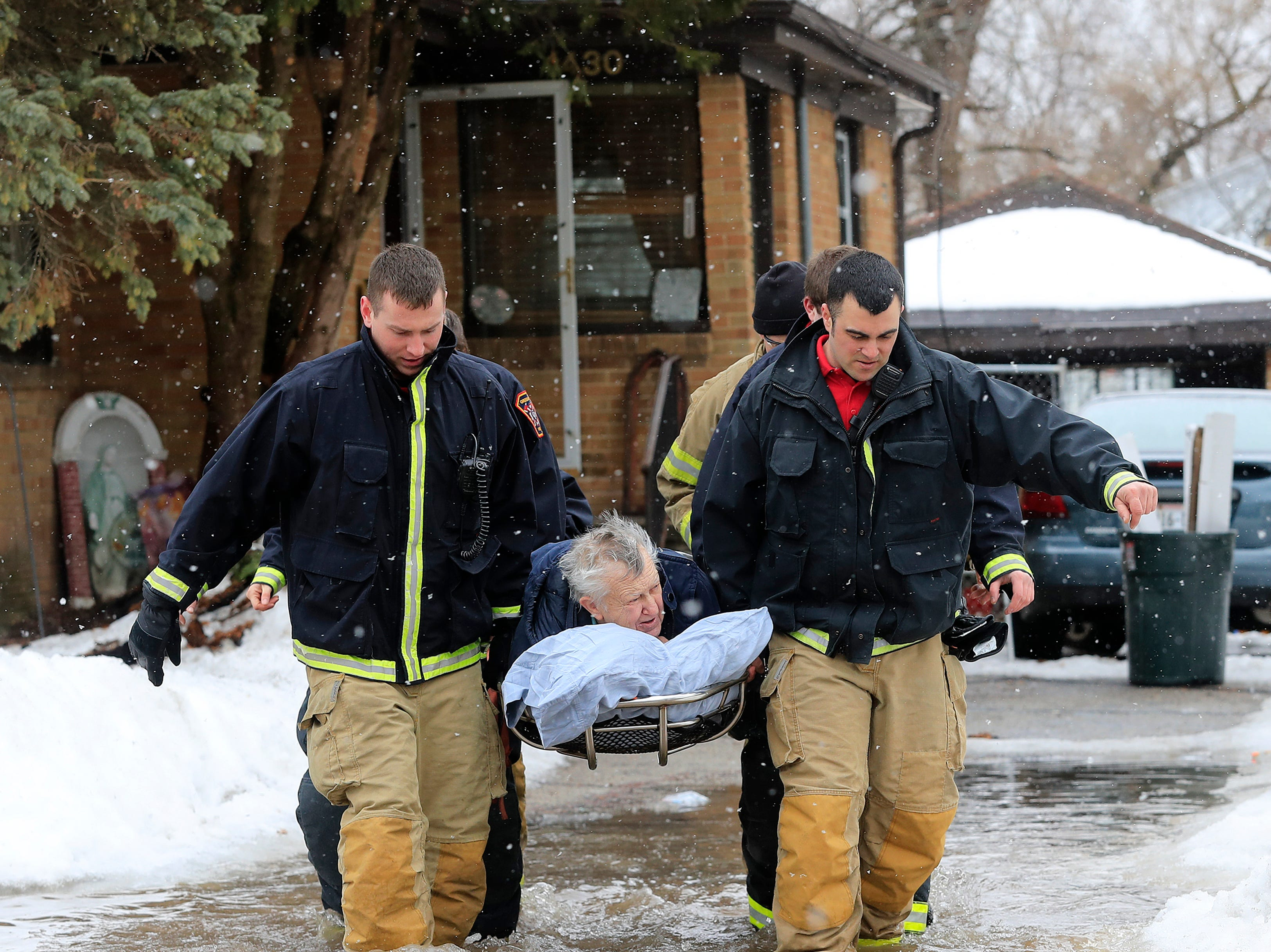 Green Bay firefighters assist residents on Crooks Street in evacuating their homes due to East river floodwaters on Friday, March 15, 2019 in Green Bay, Wis.
