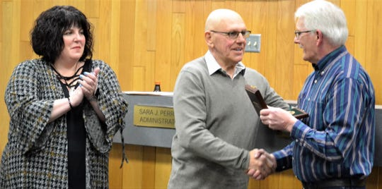Oconto Mayor Lloyd Heier, center, congratualtes Eugene Stamsa of Oconto, after presenting Stamsta with a Carnegie Hero Fund medal on March 12.   Stamsta was recognized for rescuing a woman from drowning in 2017.