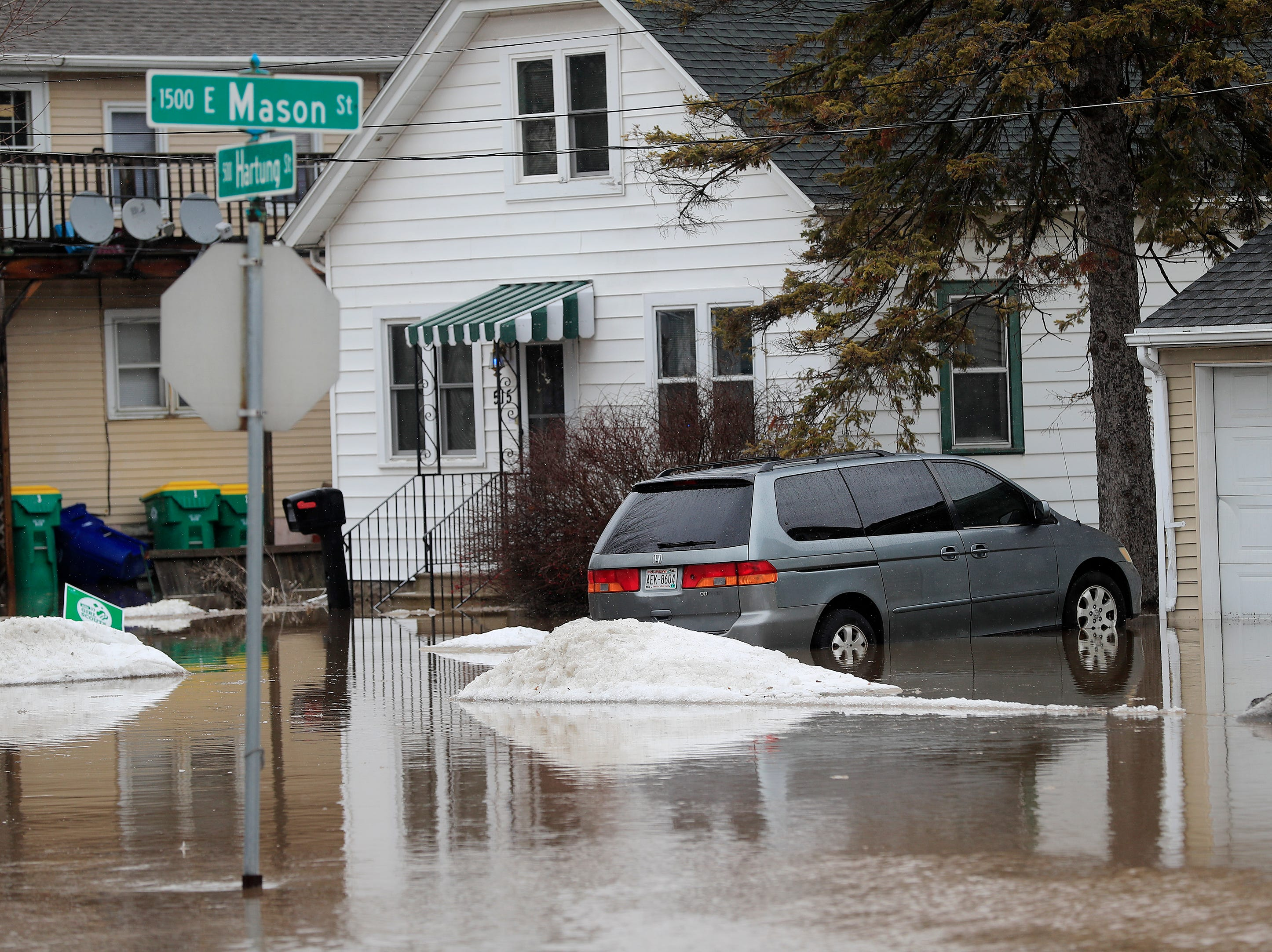 A vehicle is parked in standing water near the East river on Friday, March 15, 2019 in Green Bay, Wis.