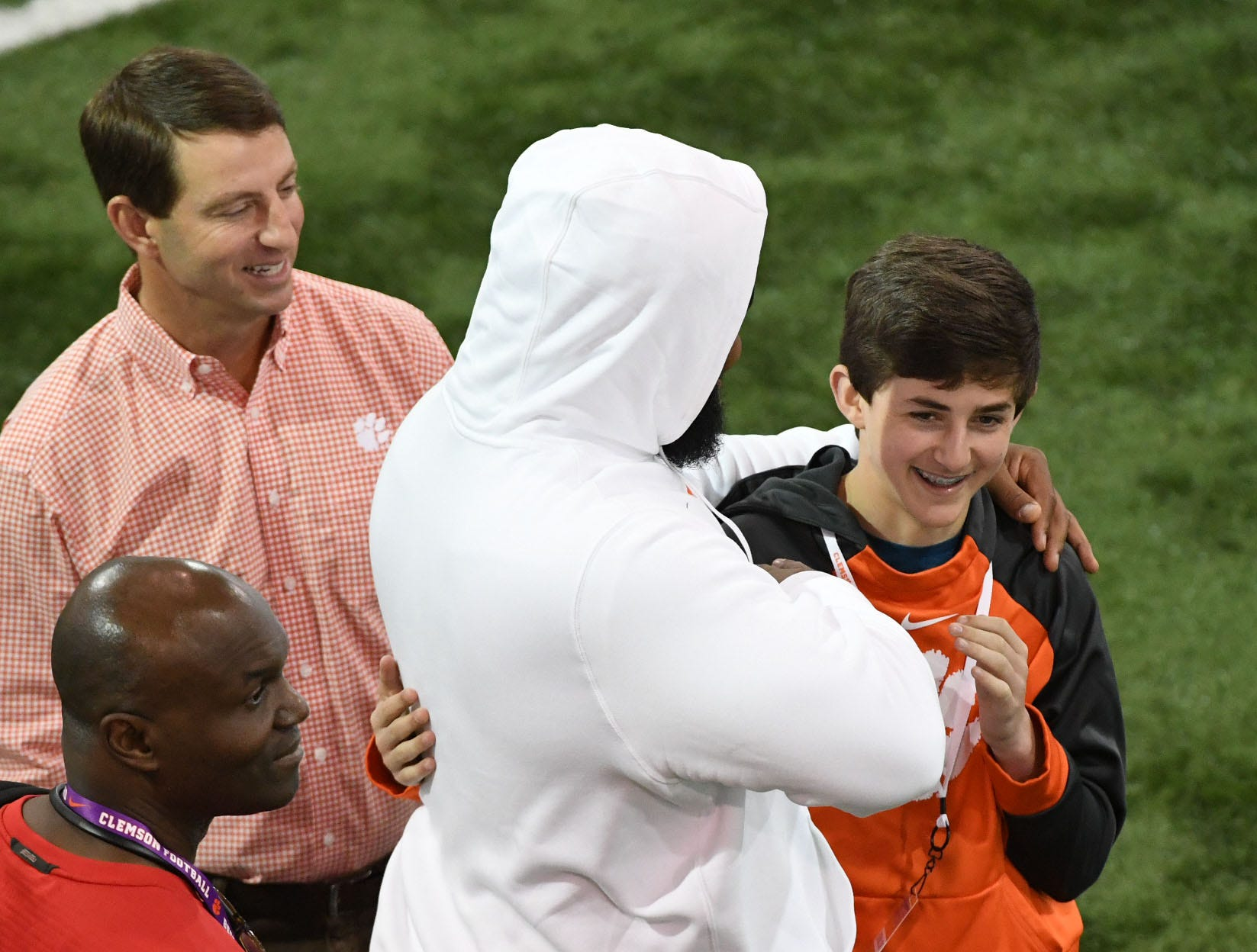 Clemson coach Dabo Swinney, left, watches NFL prospect Christian Wilkins hug his youngest son Clay Swinney, a freshman at D.W. Daniel High School, during Clemson Pro Day at the Poe Indoor Facility in Clemson, S.C. Thursday, March 14, 2019.