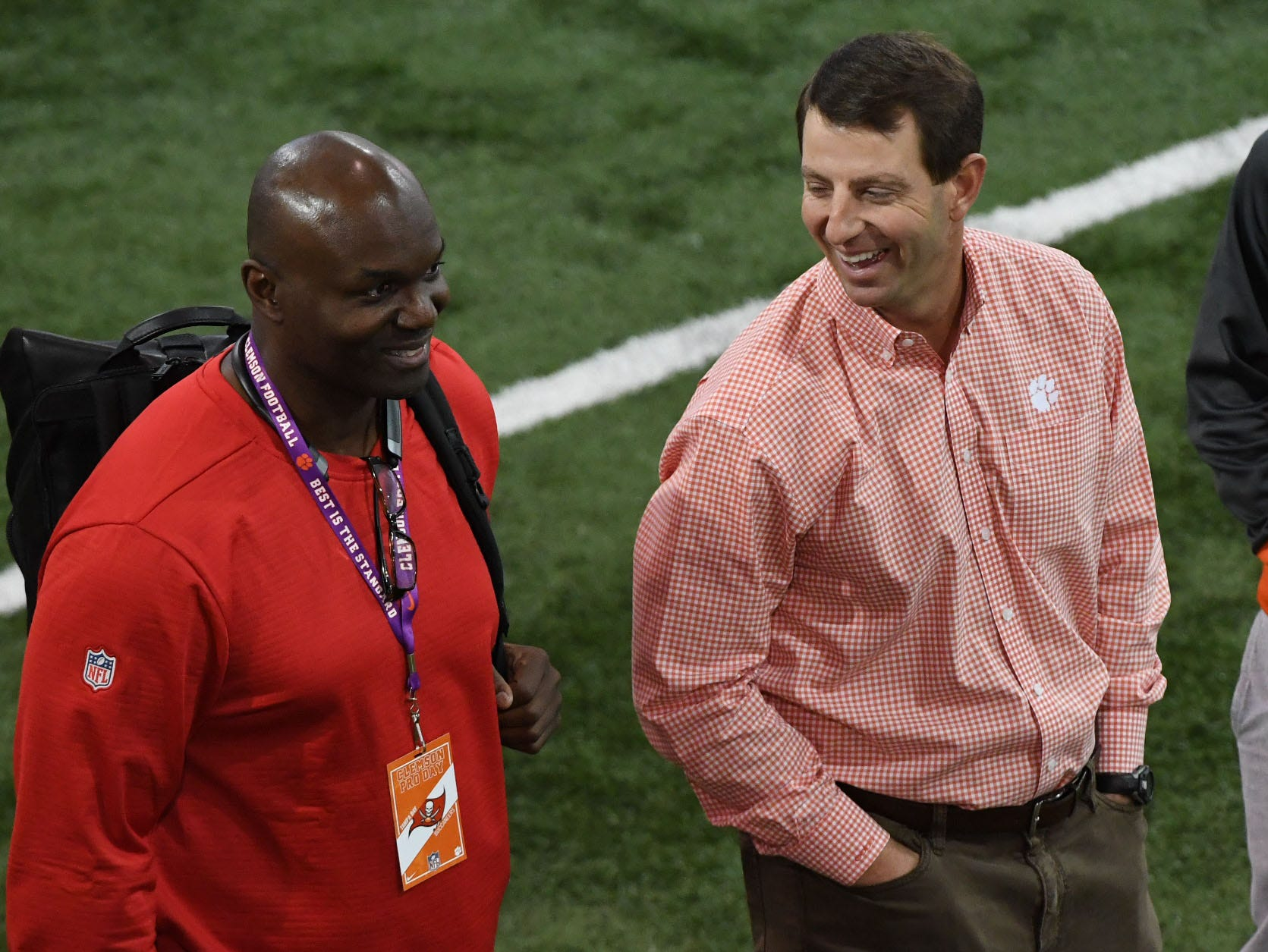 Clemson head football coach Dabo Swinney, right, talks with NFL scout from Tampa Bay during Clemson Pro Day at the Poe Indoor Facility in Clemson, S.C. Thursday, March 14, 2019.