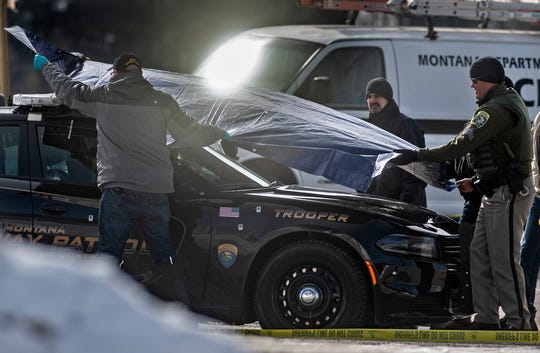 Law enforcement officers cover Montana State Trooper Wade Palmer's car at the scene of the shooting near the Evaro Bar on Friday morning.