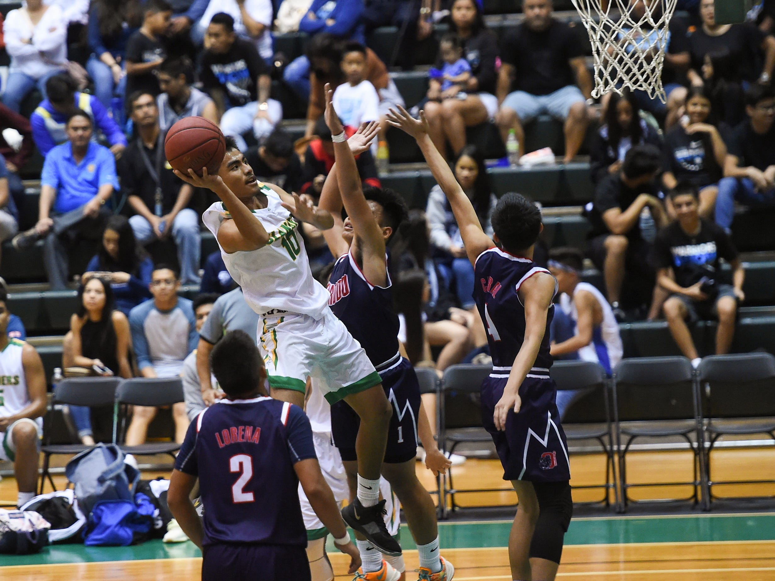 The Okkodo Bulldogs battle the John F. Kennedy Islanders during a IIAAG Boys' Basketball consolation game at the University of Guam Calvo Field House in Mangilao, March 15, 2019.