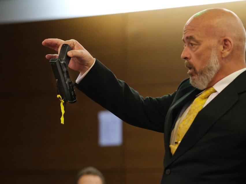Former Lt. Gov. Ray Tenorio's lawyer, Tom Fisher, demonstrates how Tenorio held the handgun in Tenorio's trial on March 15, 2019.