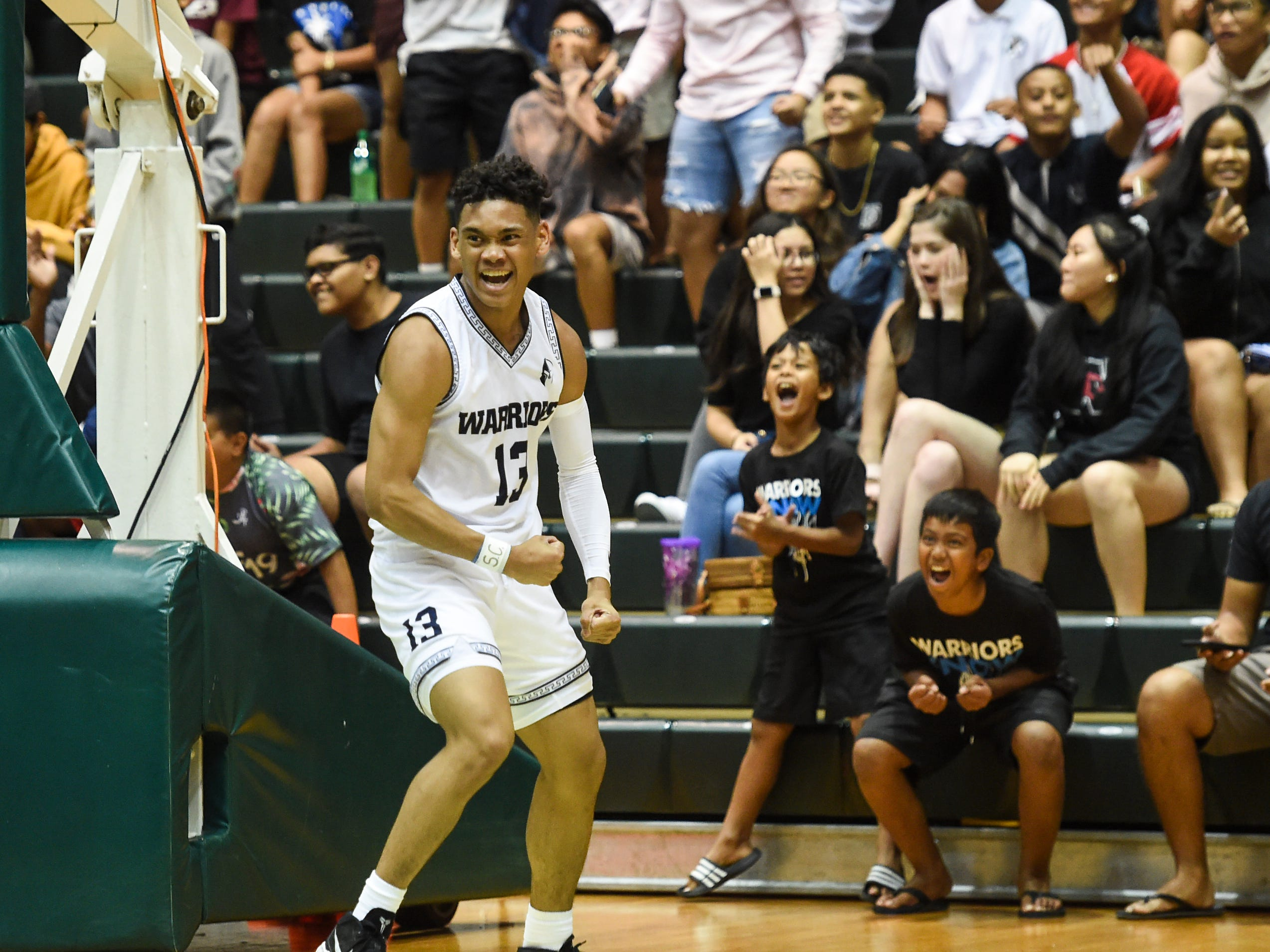 The St. Paul Warriors' Jahmar White (13) celebrates after a fast break bucket during the IIAAG Boys' Basketball Championship game against the Father Duenas Friars at the University of Guam Calvo Field House in Mangilao, March 15, 2019.