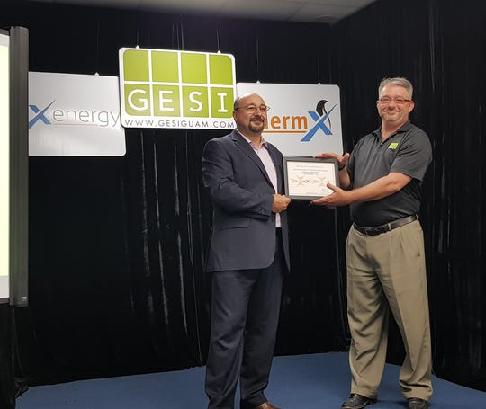 SolX Energy executive Chris Micallef hands a certificate of exclusive distribution rights to Lynn Scott of Green Energy Solutions Inc.