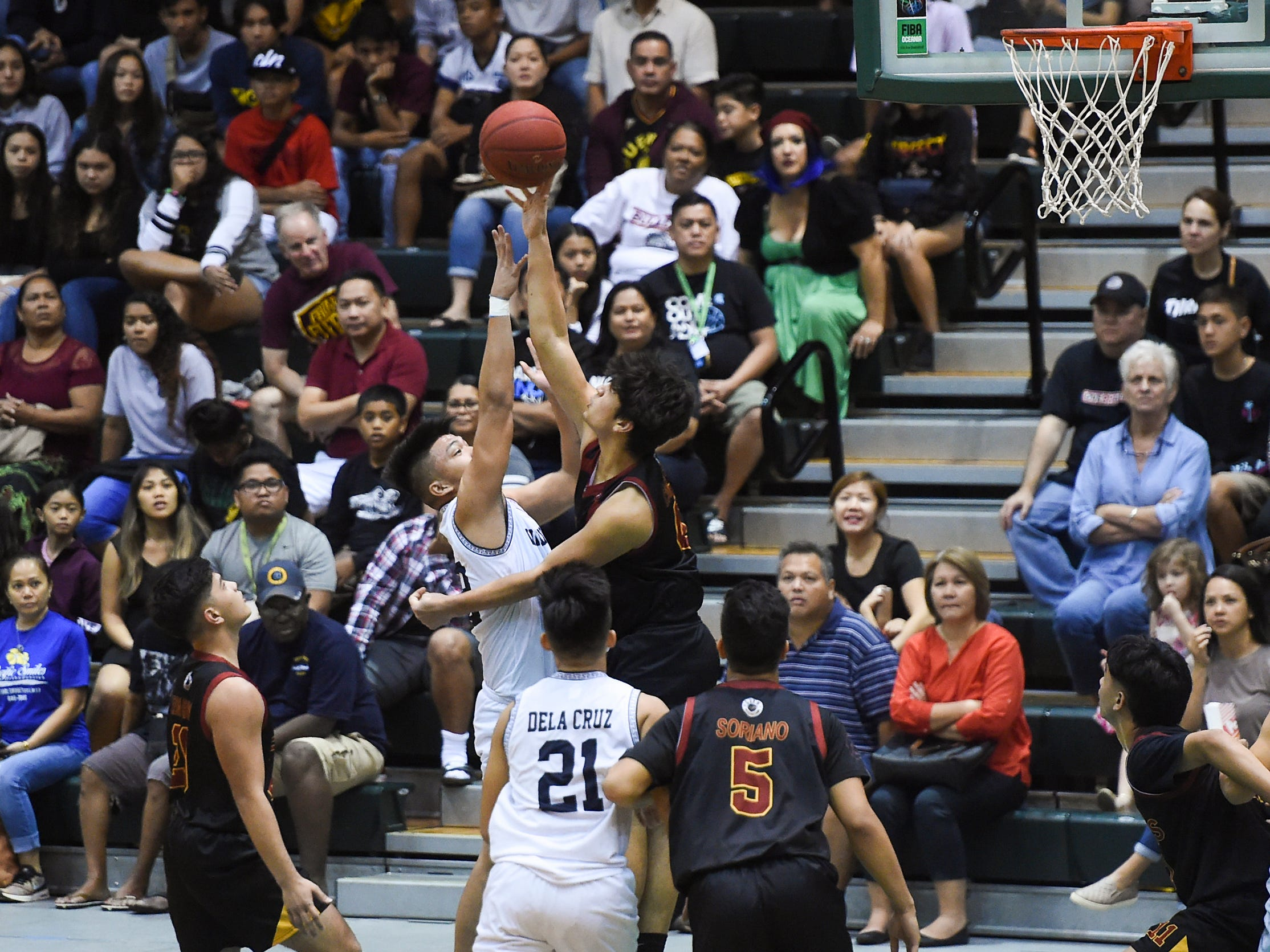 Father Duenas' Kyle Camacho blocks a shot against the St. Paul Warriors during the IIAAG Boys' Basketball Championship game at the University of Guam Calvo Field House in Mangilao, March 15, 2019.