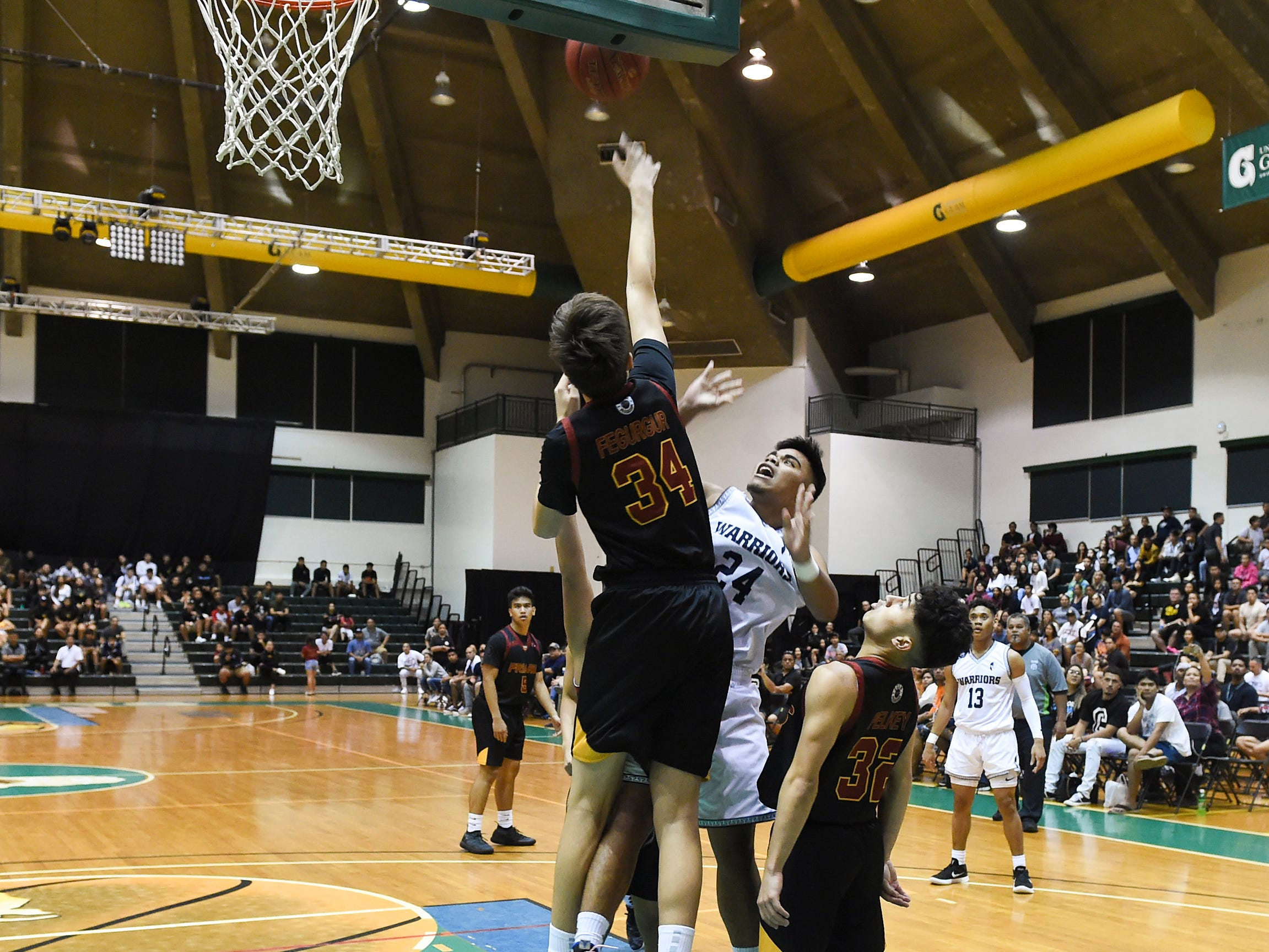 Father Duenas' Matthew Fegurgur (34) sends the ball away on a shot from St. Paul player Thelo Orichiro (24) during the IIAAG Boys' Basketball Championship game at the University of Guam Calvo Field House in Mangilao, March 15, 2019.