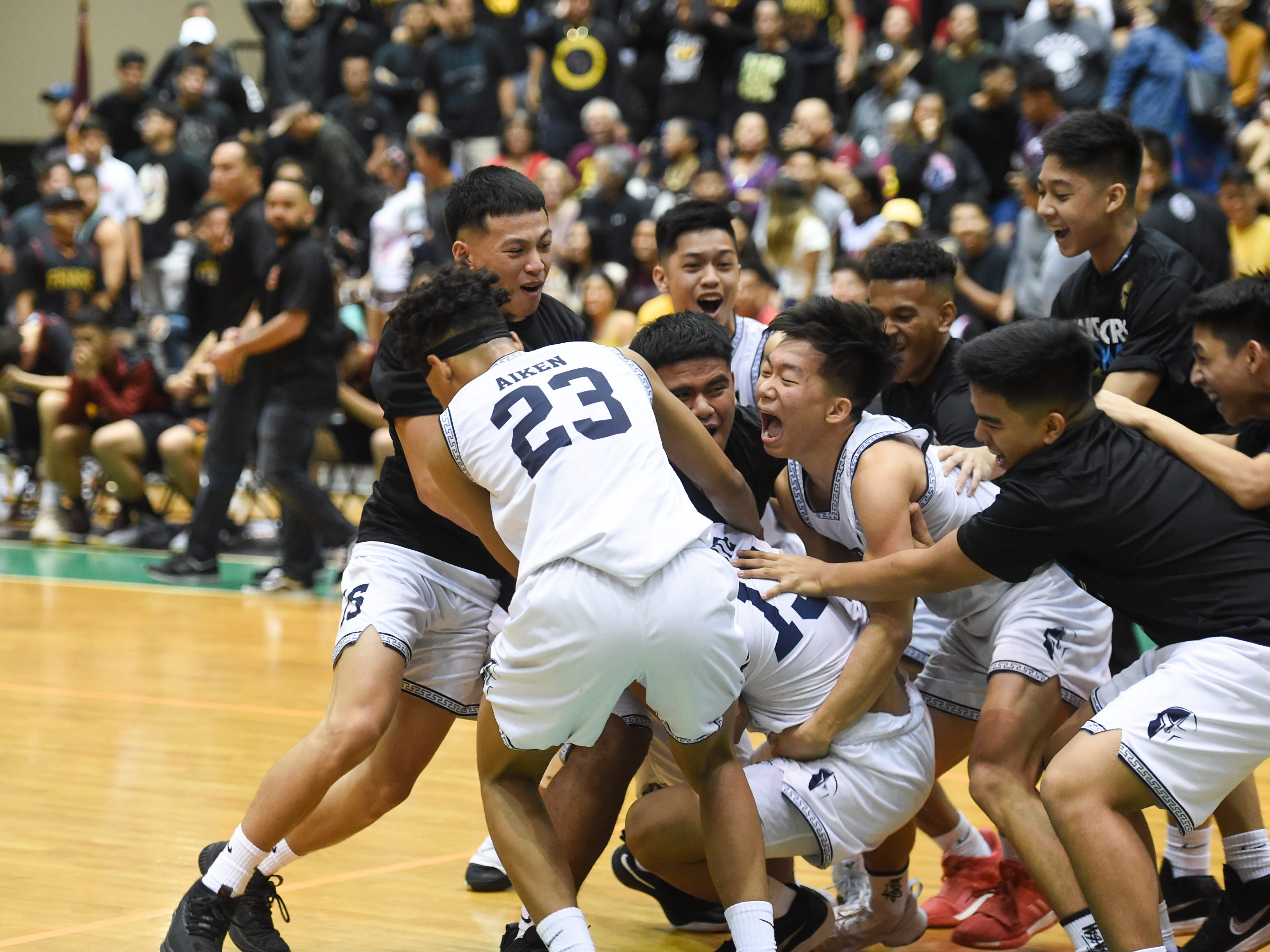 The St. Paul Warriors celebrate their 44-41 IIAAG Boys' Basketball Championship win over the Father Duenas Friars at the University of Guam Calvo Field House in Mangilao, March 15, 2019.