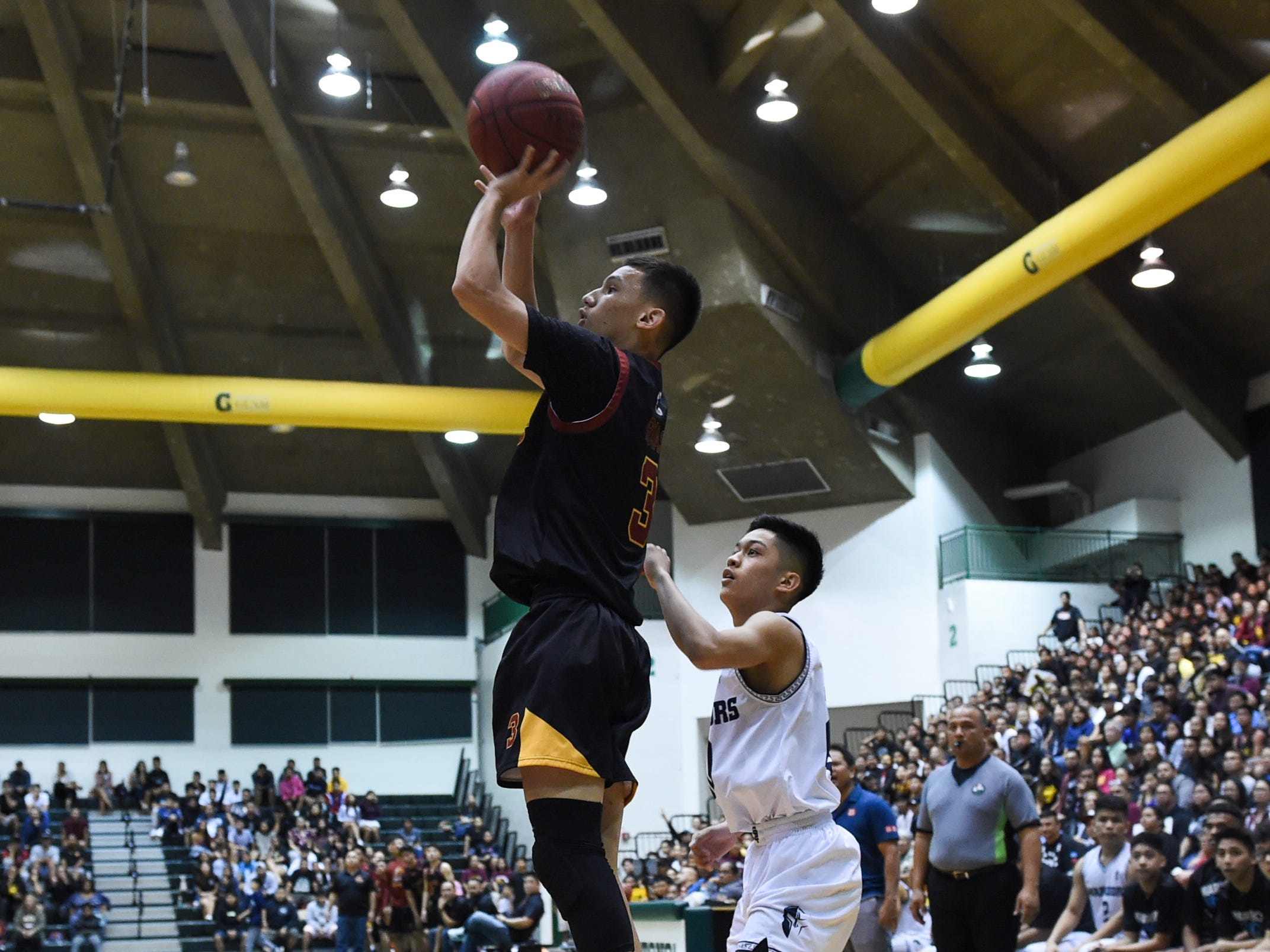 Father Duenas player Davin Rojas attempts a jump shot against the St. Paul Warriors during the IIAAG Boys' Basketball Championship game at the University of Guam Calvo Field House in Mangilao, March 15, 2019.