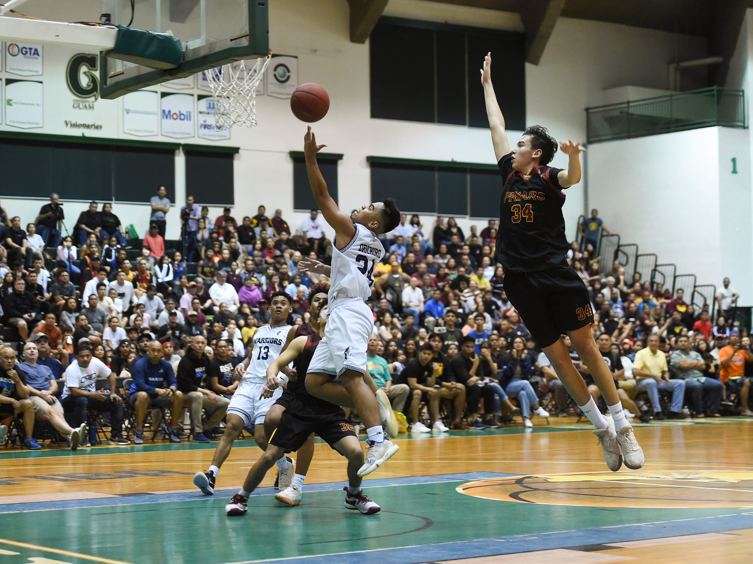 St. Paul Warriors player Thelo Orichiro (24) attempts a layup against the Father Duenas Friars during the IIAAG Boys' Basketball Championship game at the University of Guam Calvo Field House in Mangilao, March 15, 2019.