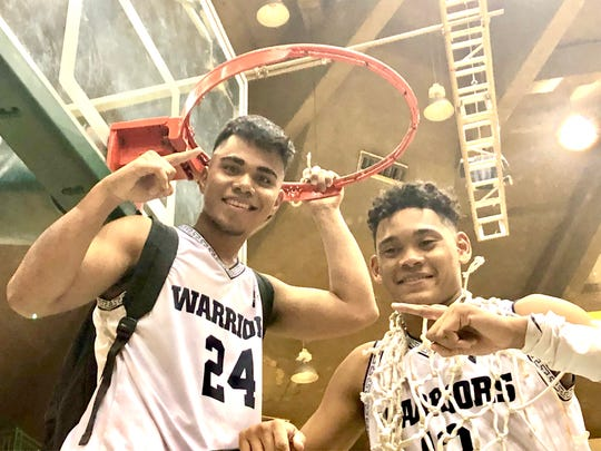 No. 24 Thelo Orichiro and No. 13 Jahmar White smile at the rim following the Saint Paul Christian School Warriors'  44-41 victory over the Father Duenas Memorial School Friars to claim the 2019 IIAAG High School Boys Basketball championship, held March 15 at the UOG Calvo Fieldhouse. Orichiro had eight assists and White scored 28 points to lead the Warriors in a thriller that went down to the final minute.