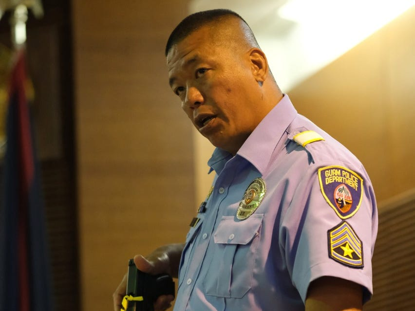 Sgt. Carl Cruz, Guam Police Department, holds a handgun that is evidence as he takes the stand in trial of former Lt. Gov. Ray Tenorio on March 15, 2019.