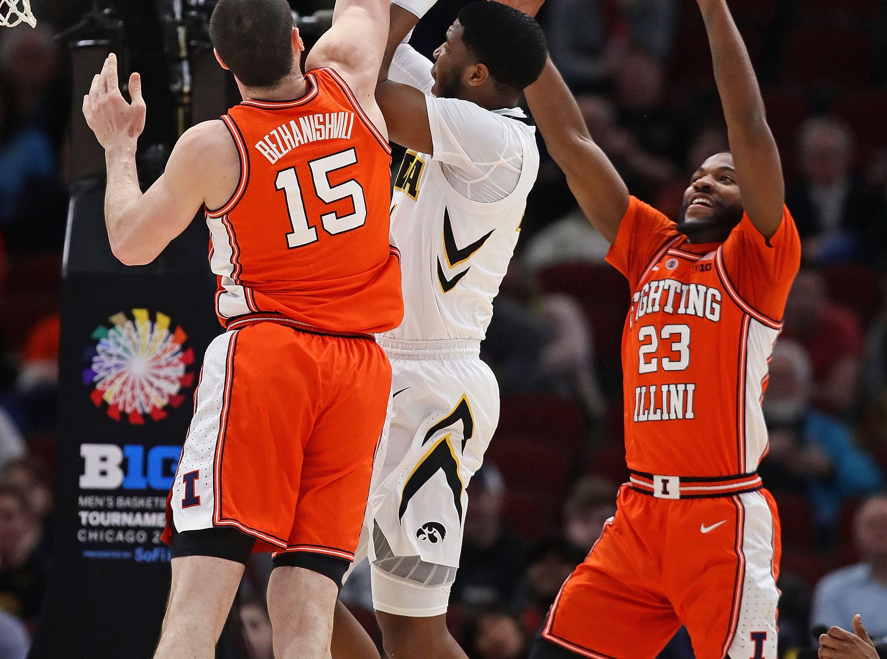 CHICAGO, ILLINOIS - MARCH 14: Isaiah Moss #4 of the Iowa Hawkeyes shoots between Giorgi Bezhanishvili #15 and Aaron Jordan #23 of the Illinois Fighting Illini at the United Center on March 14, 2019 in Chicago, Illinois.  (Photo by Jonathan Daniel/Getty Images)