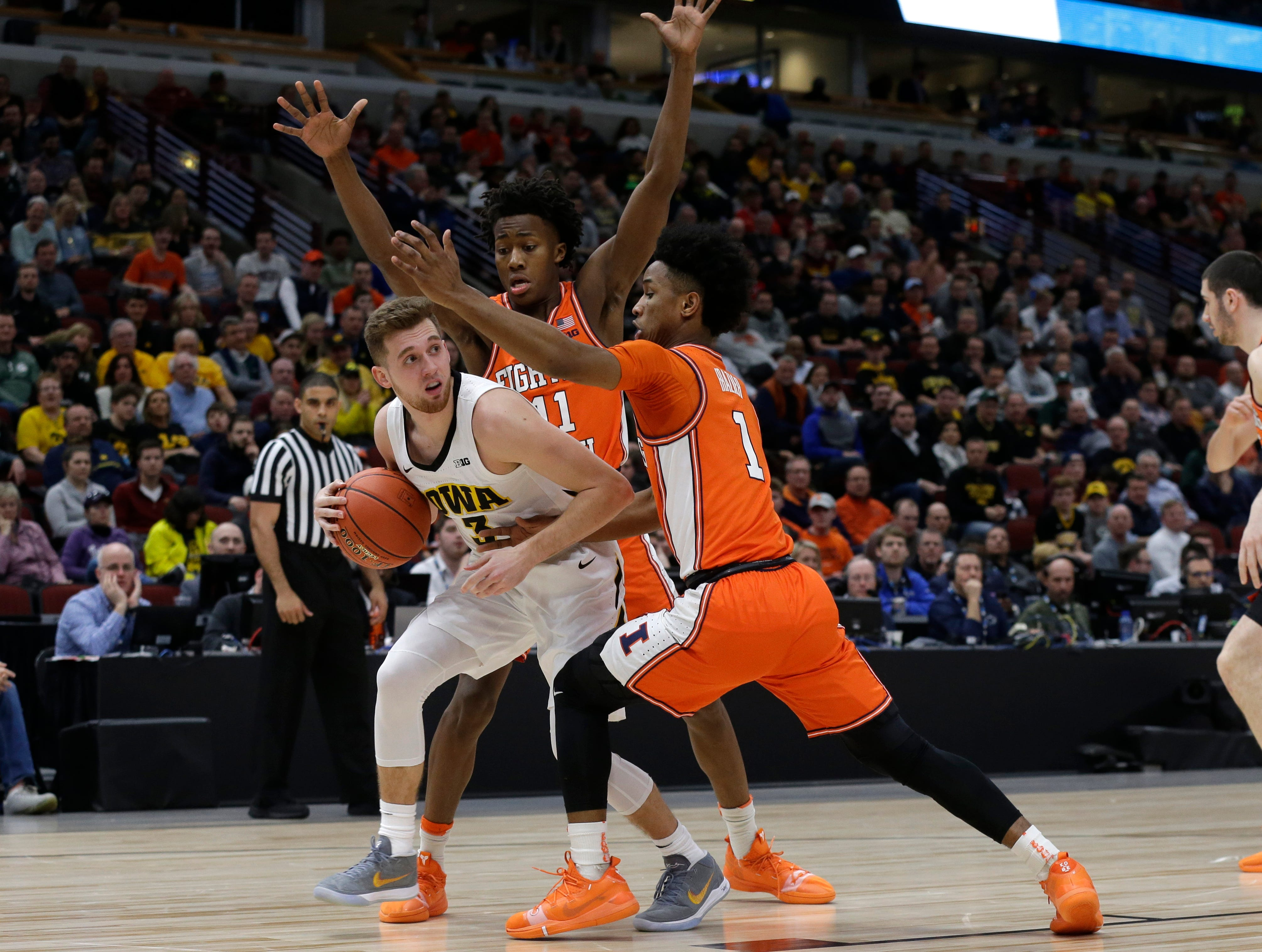 Iowa's Jordan Bohannon (3) looks to pass against Illinois's Ayo Dosunmu (11) and Trent Frazier (1) during the first half of an NCAA college basketball game in the second round of the Big Ten Conference tournament, Thursday, March 14, 2019, in Chicago. (AP Photo/Kiichiro Sato)