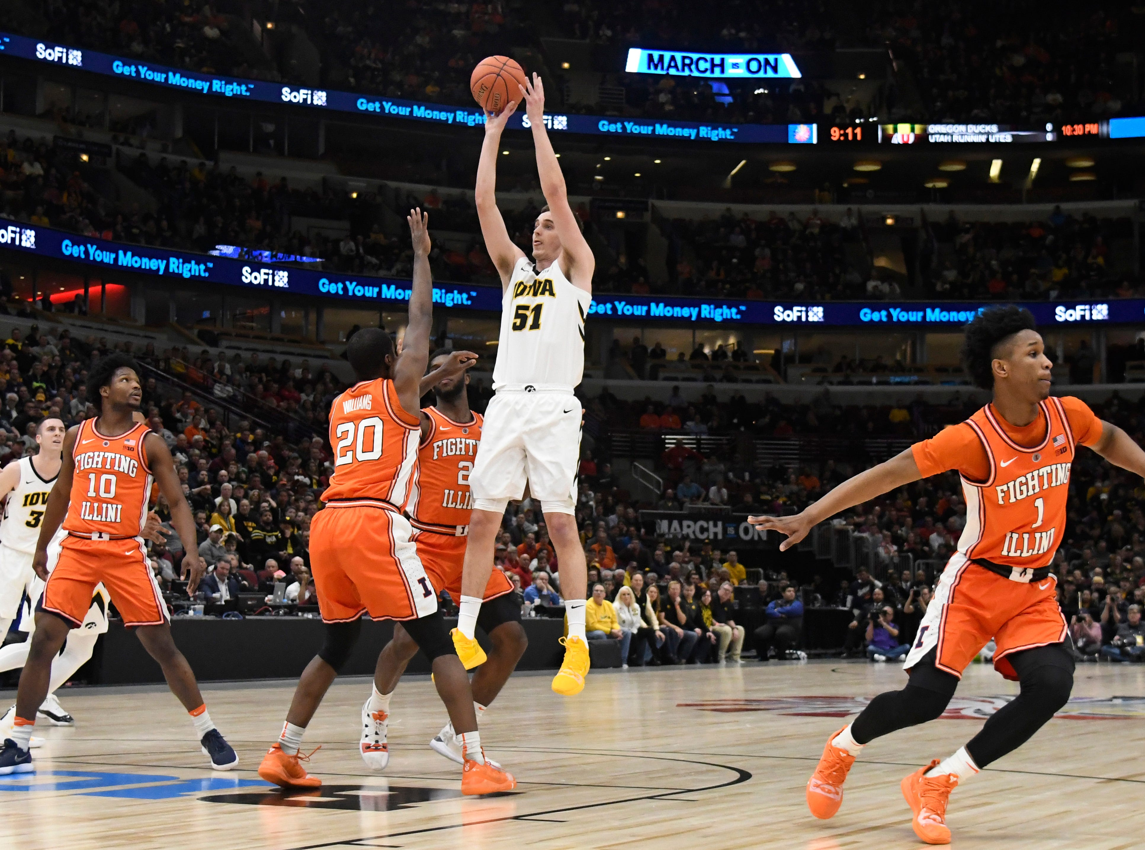 Mar 14, 2019; Chicago, IL, USA; Iowa Hawkeyes forward Nicholas Baer (51) shoots over Illinois Fighting Illini guard Da'Monte Williams (20) during the first half in the Big Ten conference tournament at United Center. Mandatory Credit: David Banks-USA TODAY Sports