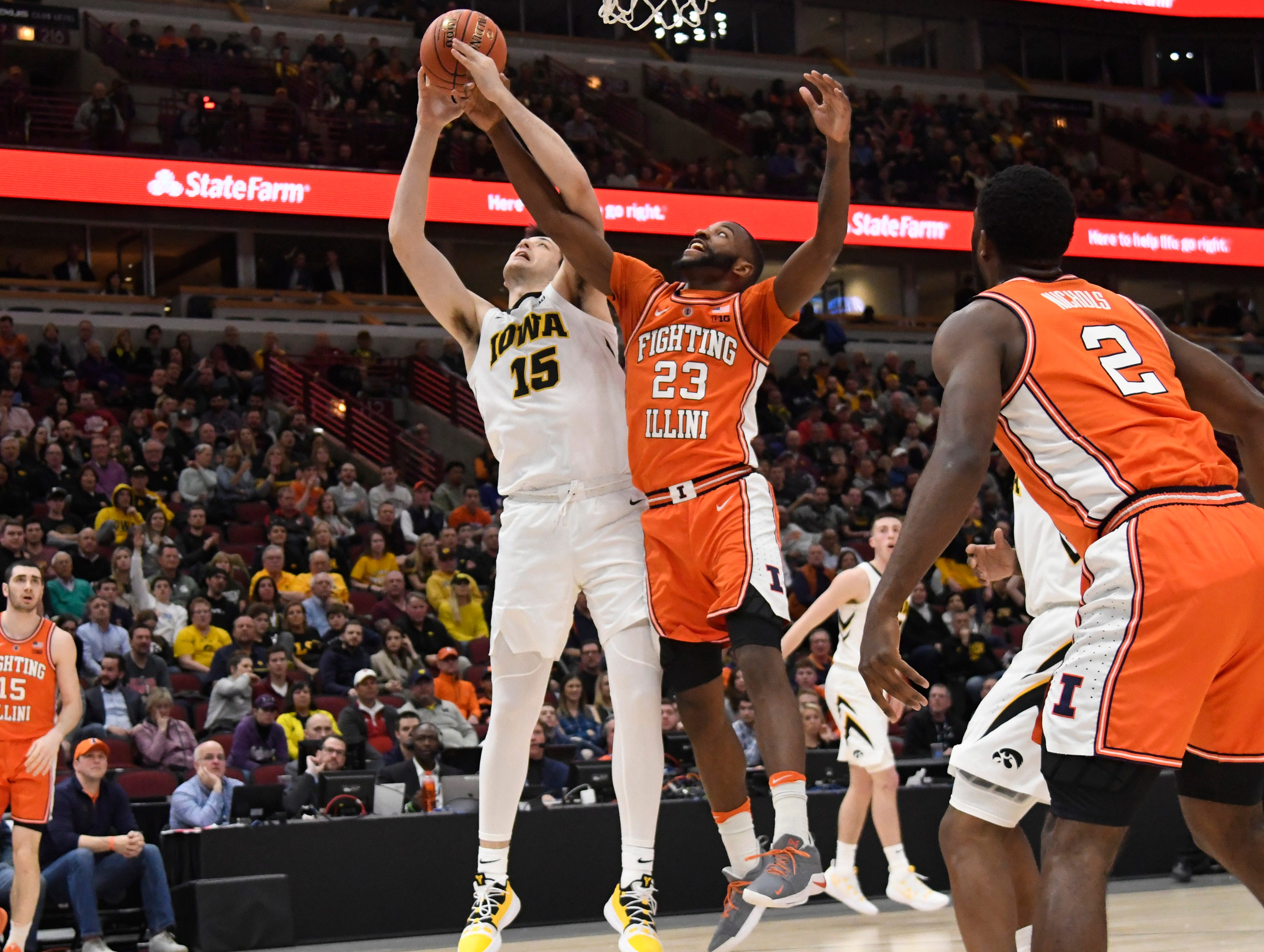 Mar 14, 2019; Chicago, IL, USA; Iowa Hawkeyes forward Ryan Kriener (15) and Illinois Fighting Illini guard Aaron Jordan (23) go for a rebound during the first half in the Big Ten conference tournament at United Center. Mandatory Credit: David Banks-USA TODAY Sports