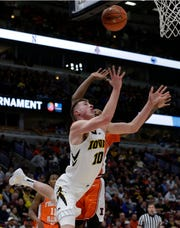 Iowa's Joe Wieskamp (10) drives for a layup and foul against Illinois's Aaron Jordan during the first half Thursday at the United Center in Chicago.