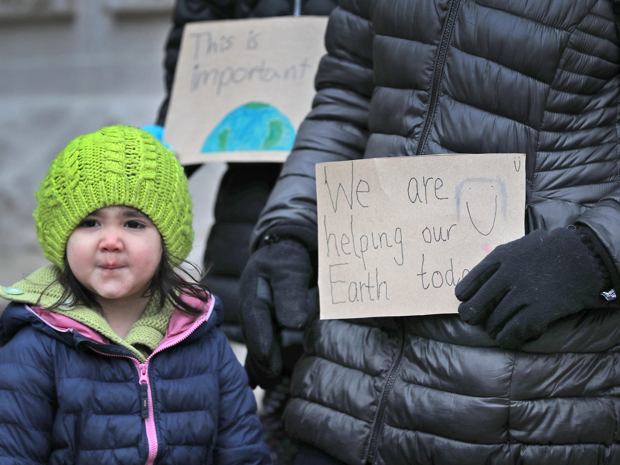 Aya Mulholland stands with her sister and mother during the Indiana part of the international Climate Strike, Friday, March 15, 2019, held outside the Indiana Statehouse.  Following in the footsteps of 16-year-old Swedish trailblazer, Greta Thunberg, students around the world are skipping school to protest government inaction on climate change.
