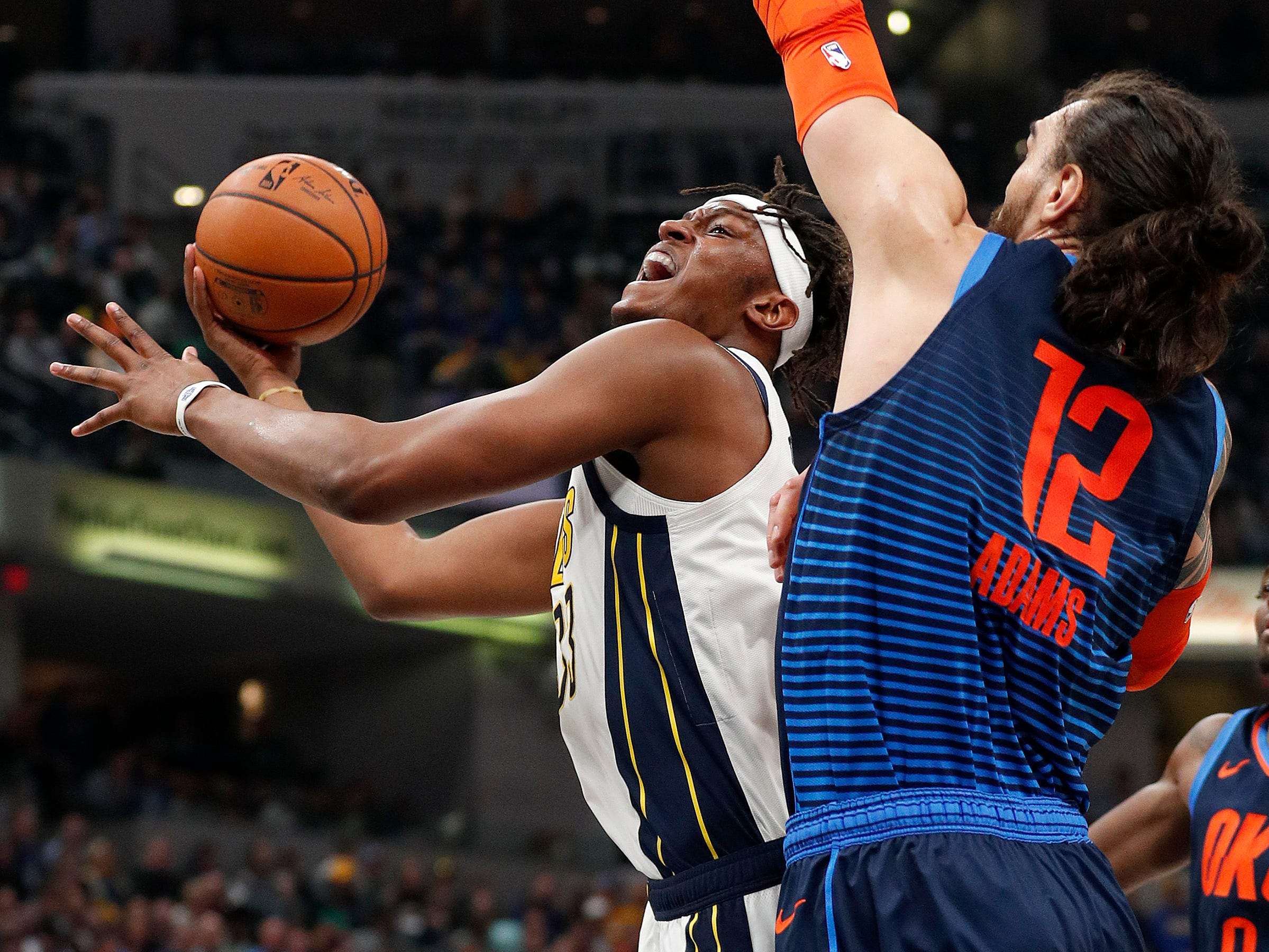Indiana Pacers center Myles Turner (33) drives to the basket around Oklahoma City Thunder center Steven Adams (12) in the first half of their game at Bankers Life Fieldhouse on Thursday, Mar. 14, 2019.