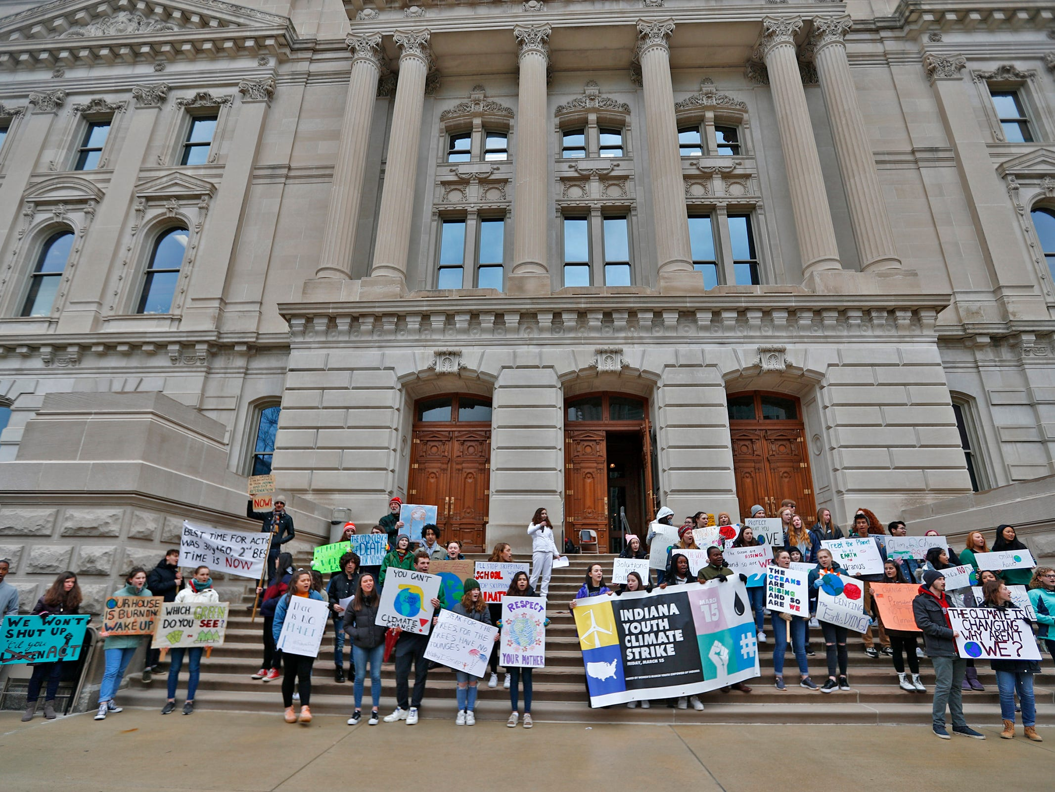 Early in the rally, students gather with signs on the sound steps of the Indiana Statehouse, during the Indiana part of the international Climate Strike, Friday, March 15, 2019, held outside the Indiana Statehouse.  Following in the footsteps of 16-year-old Swedish trailblazer, Greta Thunberg, students around the world are skipping school to protest government inaction on climate change.  The Indiana rally ended up with over 250 participants.