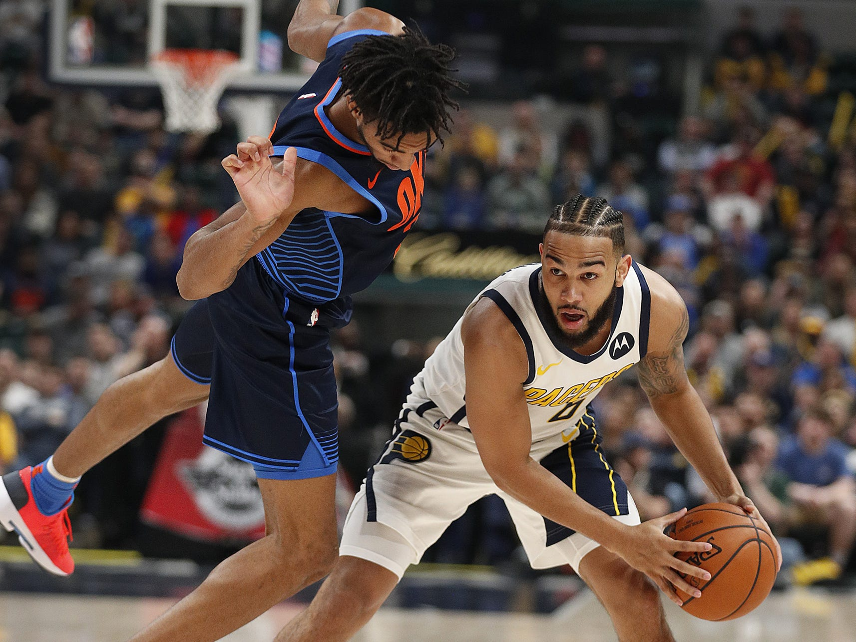 Indiana Pacers guard Cory Joseph (6) looks on as Oklahoma City Thunder guard Terrance Ferguson (23) falls over hin in the first half of their game at Bankers Life Fieldhouse on Thursday, Mar. 14, 2019.
