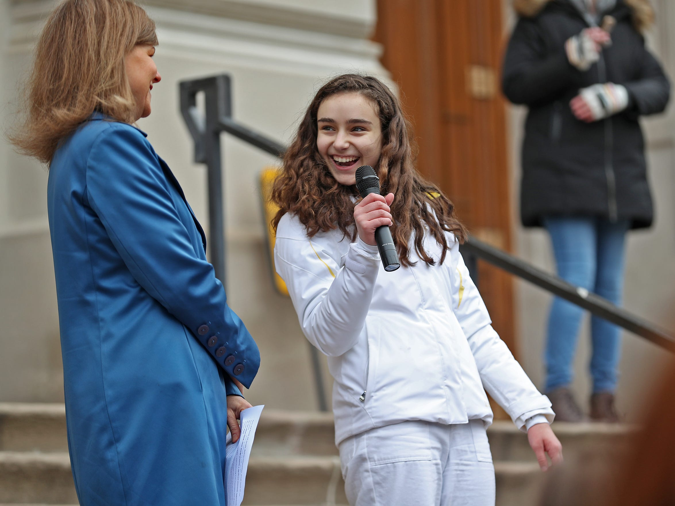 Carmel High School sophomore Isabella Fallahi, right, laughs as she introduces Indiana Representative Carey Hamilton to address the crowd during the Indiana part of the international Climate Strike, Friday, March 15, 2019, held outside the Indiana Statehouse.  Following in the footsteps of 16-year-old Swedish trailblazer, Greta Thunberg, students around the world are skipping school to protest government inaction on climate change.