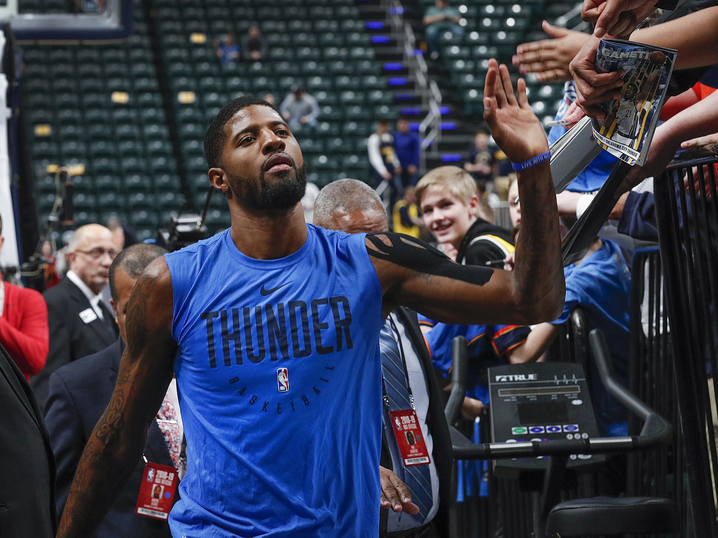 Oklahoma City Thunder forward Paul George (13) high fives some of his fans as he leaves the court following the pregame warm up before the start of their game against the Indiana Pacers at Bankers Life Fieldhouse on Thursday, Mar., 14, 2019.