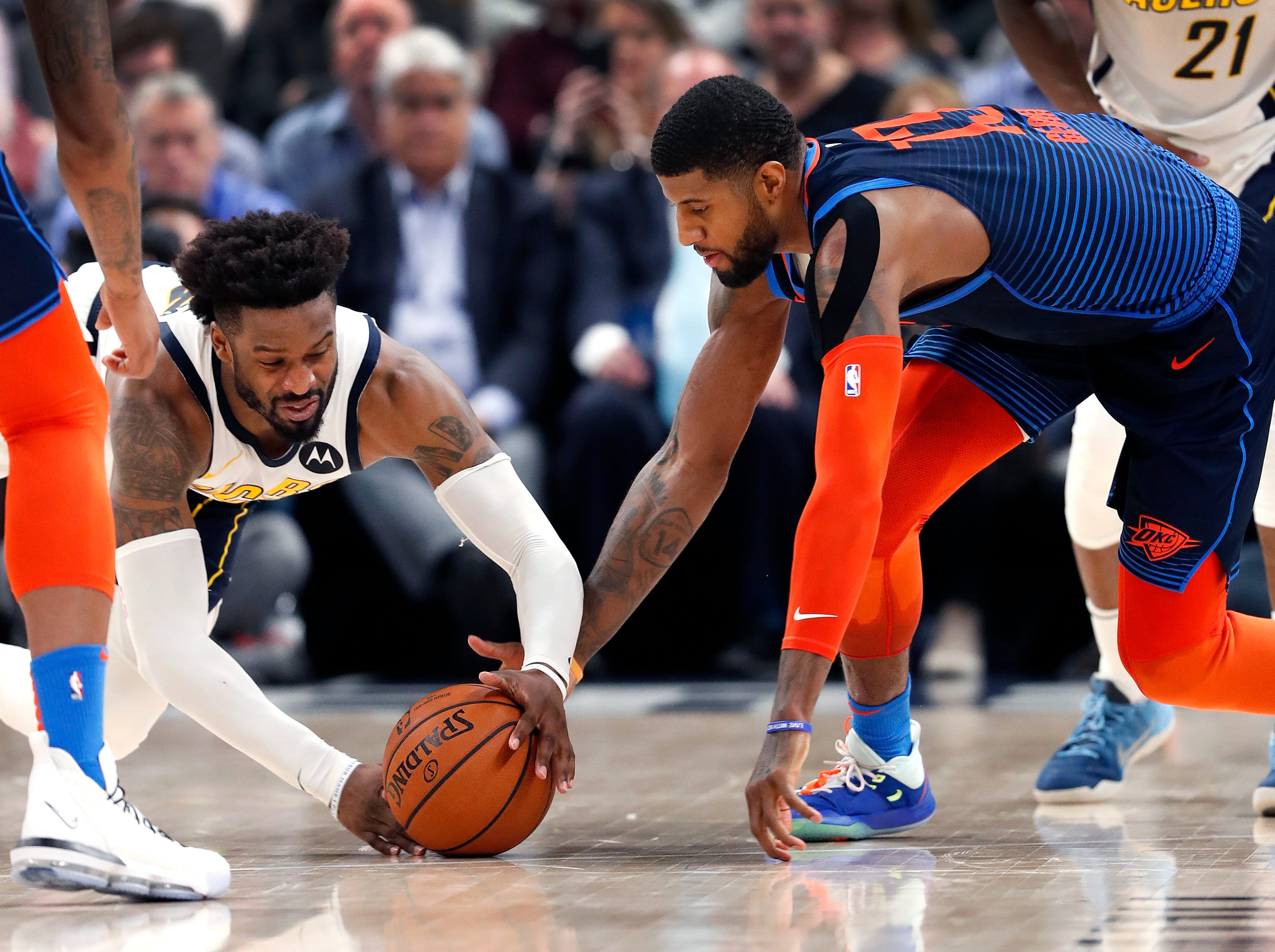 Indiana Pacers guard Wesley Matthews (23) and Oklahoma City Thunder forward Paul George (13) scramble for loose ball in the second half of their game at Bankers Life Fieldhouse on Thursday, Mar. 14, 2019. The Pacers defeated the Thunder 108-106.