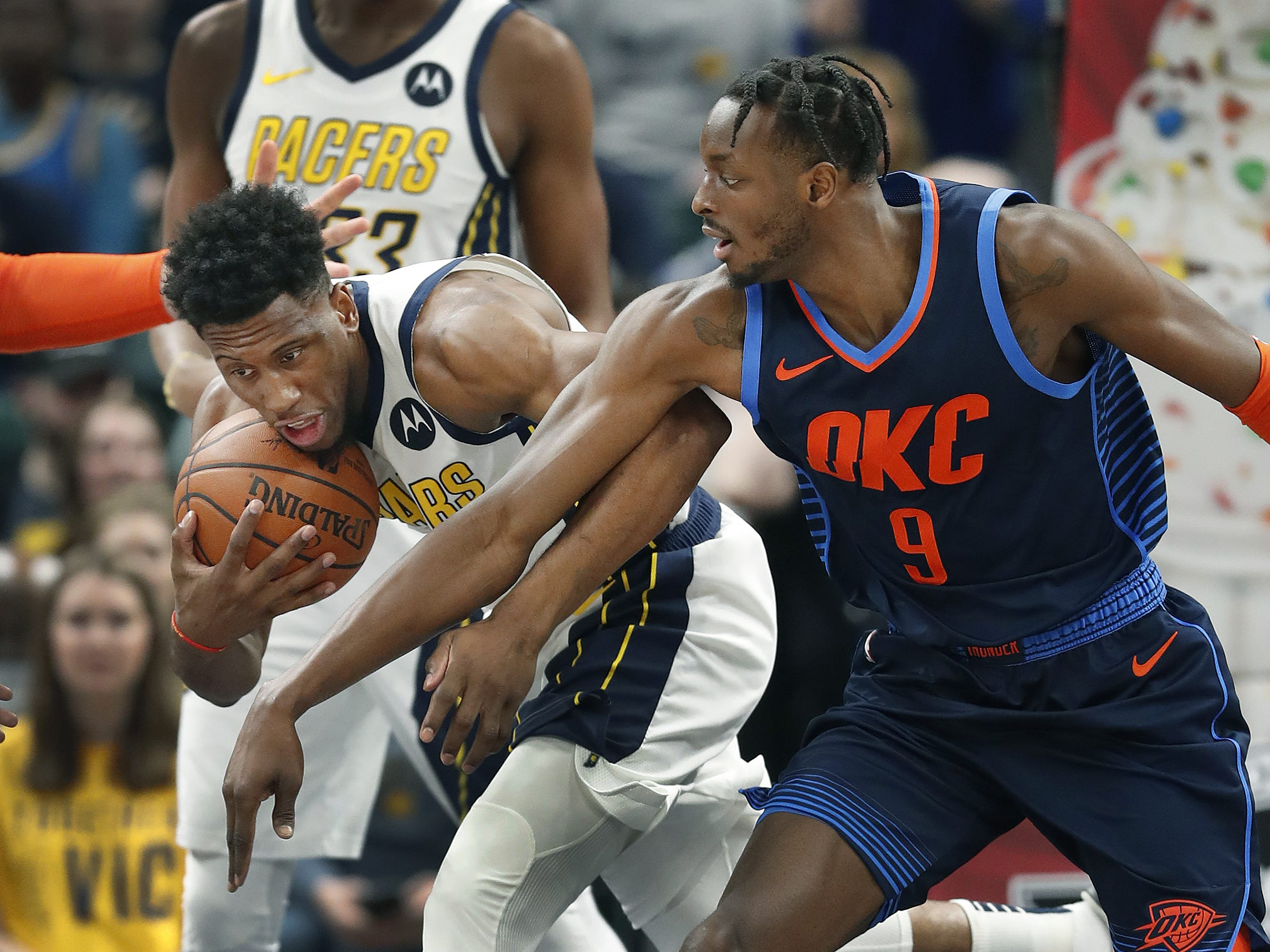 Indiana Pacers forward Thaddeus Young (21) pulls a rebound away from Oklahoma City Thunder forward Jerami Grant (9) in the first half of their game at Bankers Life Fieldhouse on Thursday, Mar. 14, 2019.